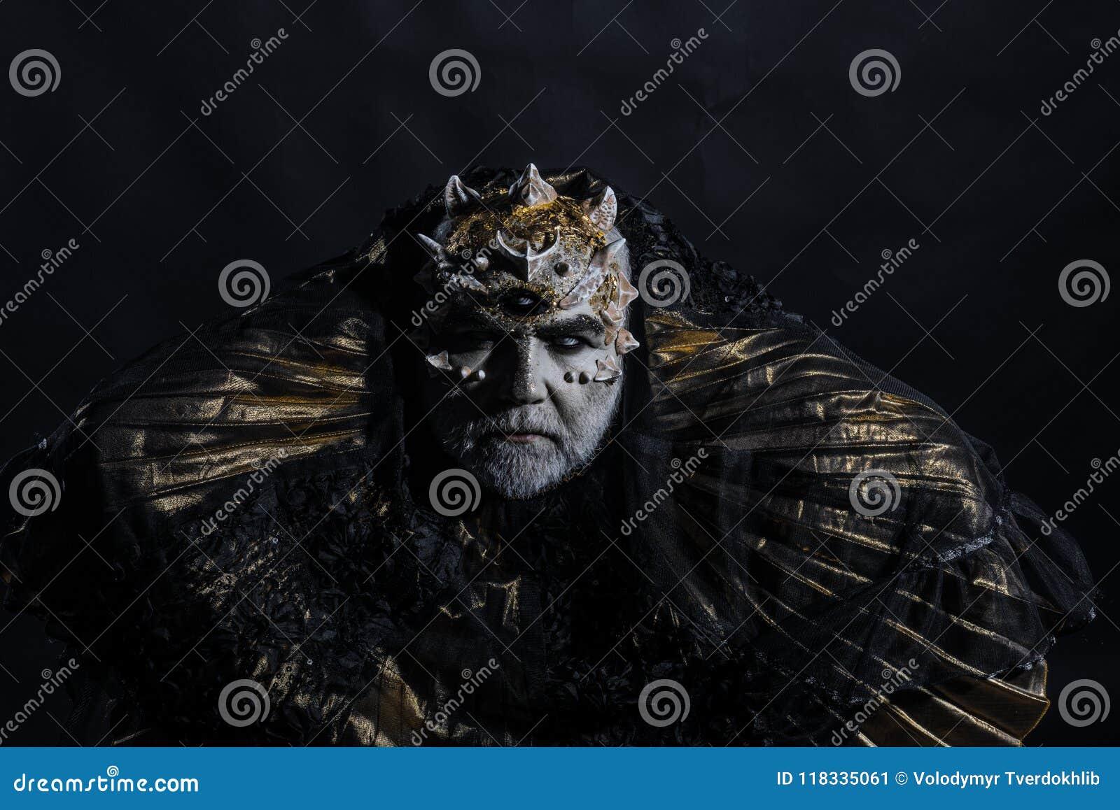 Alter König der Märchenwelt sitzend auf Thron, Fantasiekonzept Alte bärtige Blinderdornen auf seinem Kopf lokalisiert