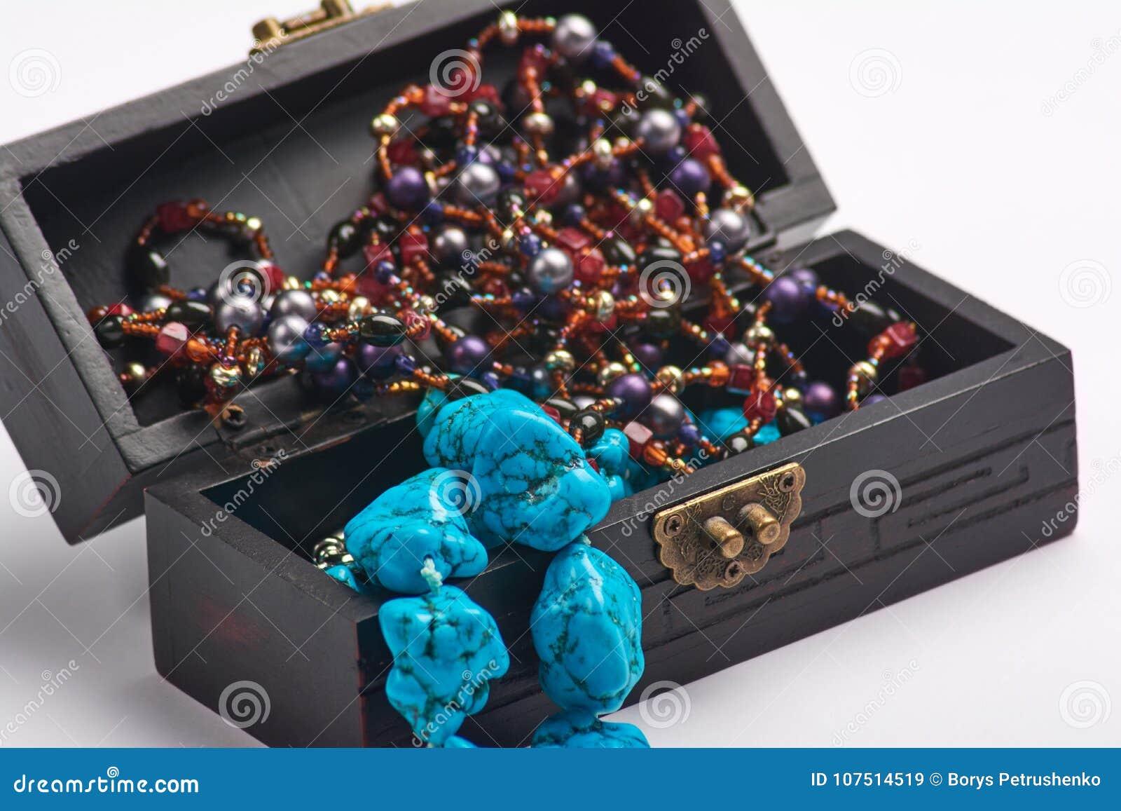 Alter Kasten des Schmucks und blaue Perlenhalskette Getrennt auf einem weißen Hintergrund