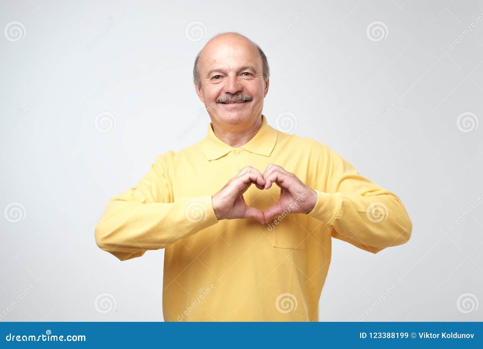Alter kaukasischer Mann im gelben T-Shirt, das aus Handherzen heraus macht