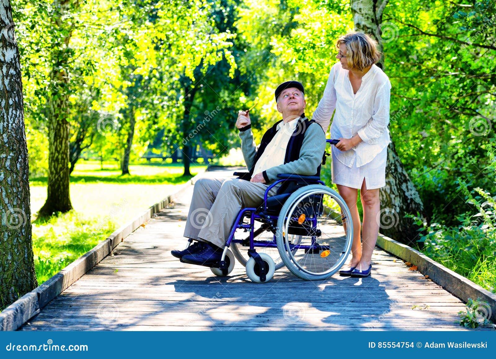Alter Mann auf Rollstuhl und junger Frau im Park