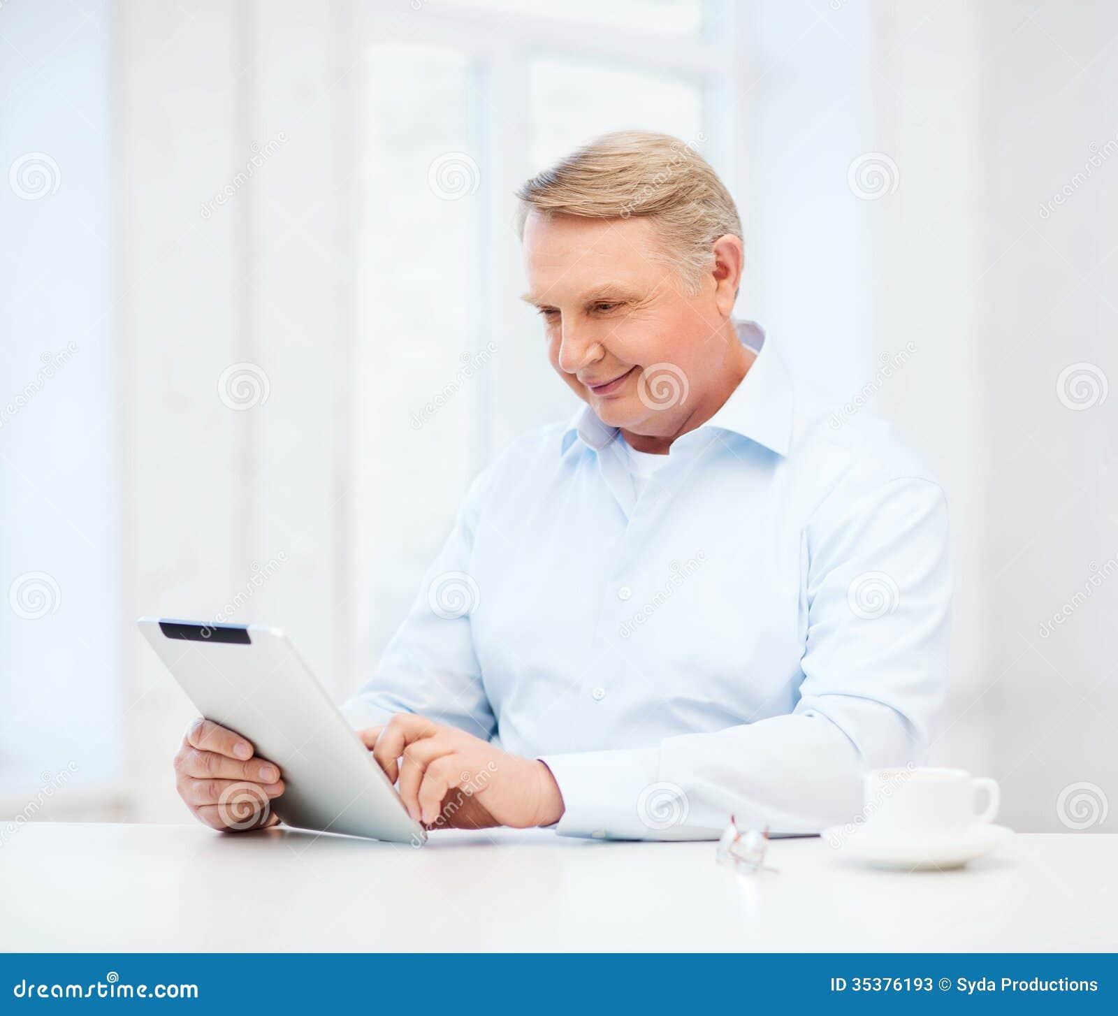 Tragende brillen des alten mannes mit tabletten pc computer zu hause