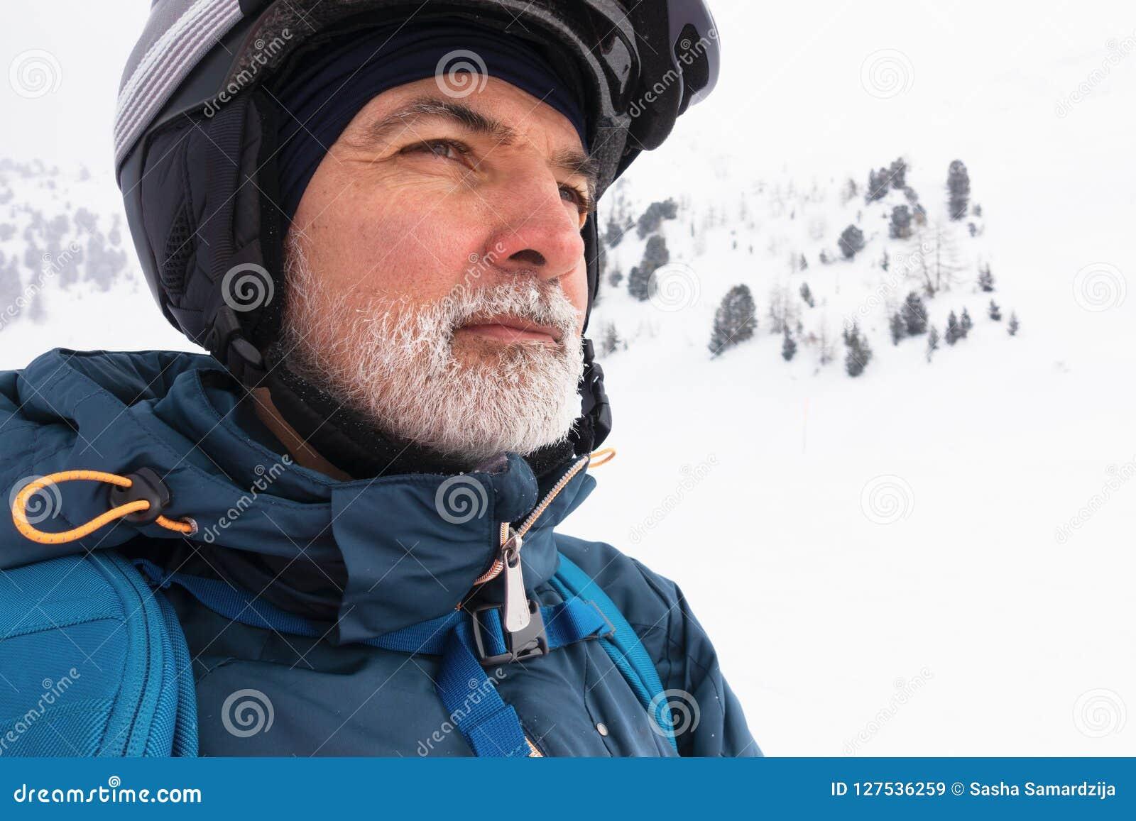 Alter Mann mit weißem Bart auf schneebedecktem Berg