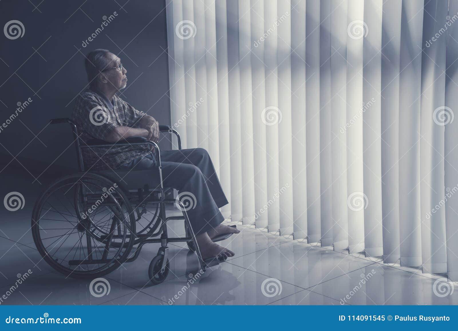 Alter Mann sitzt auf Rollstuhl beim Träumen