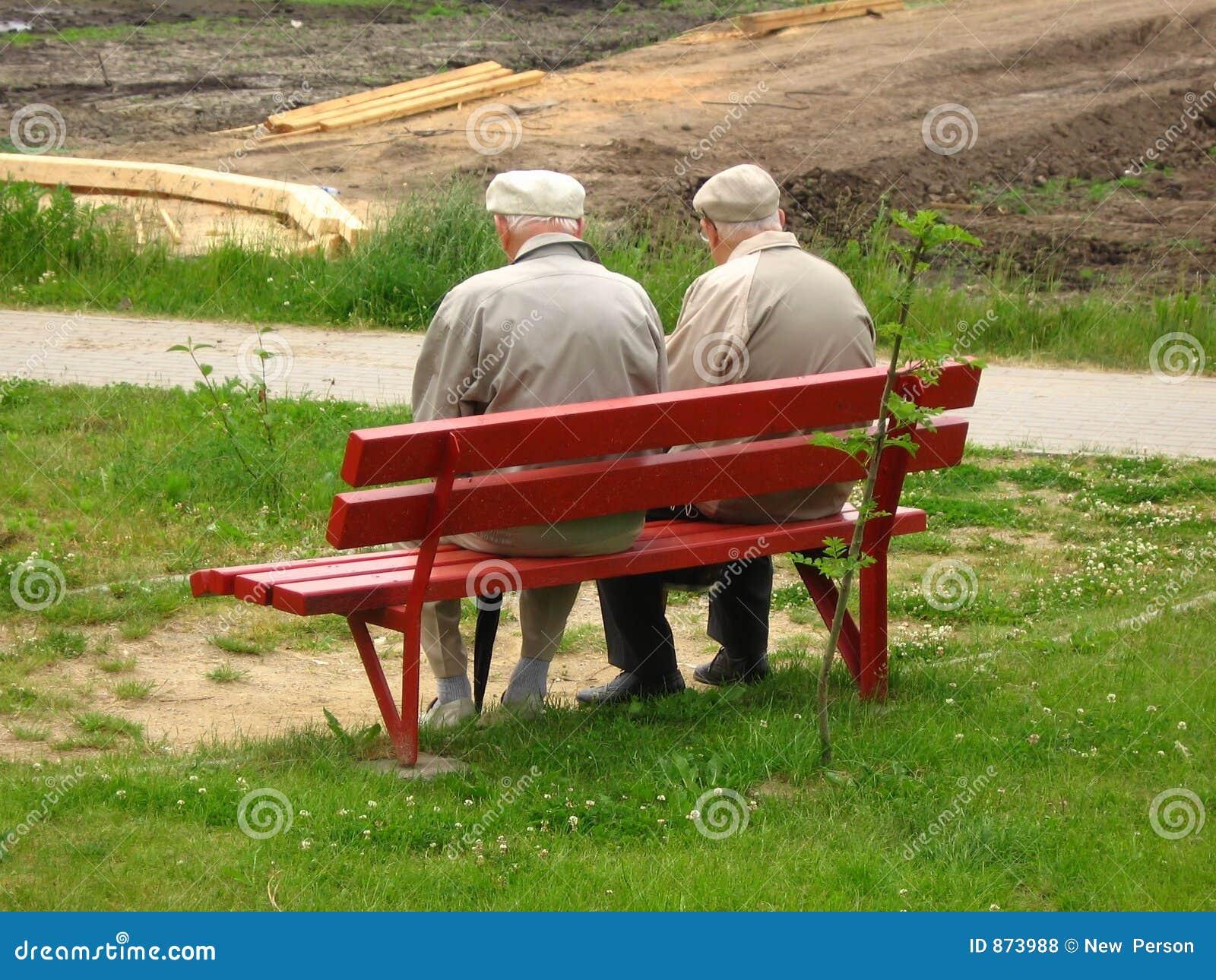 Alter Mann zwei, der auf der Bank sitzt