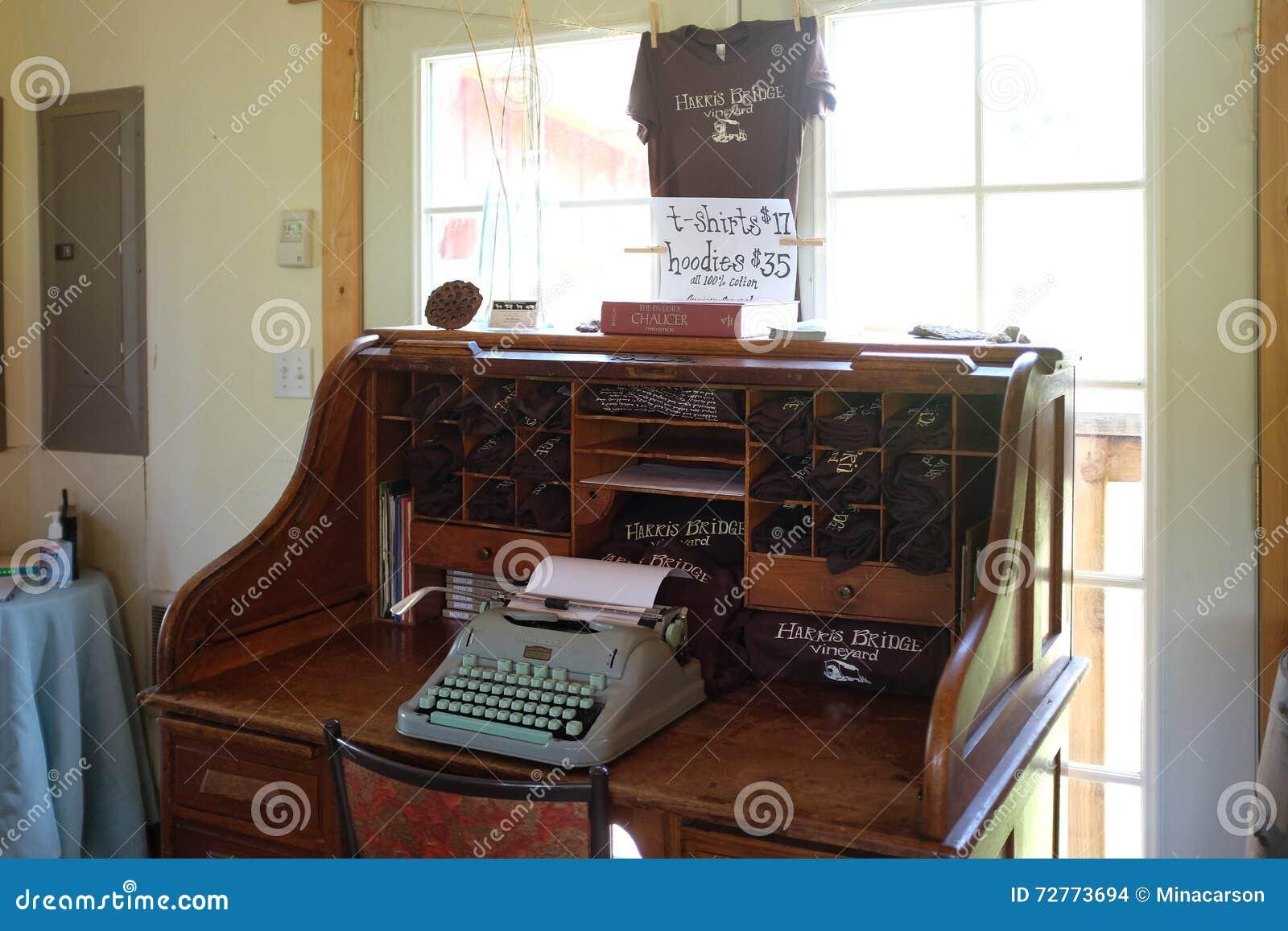 alter schreibtisch mit schreibmaschinen- und touristenhemden an der