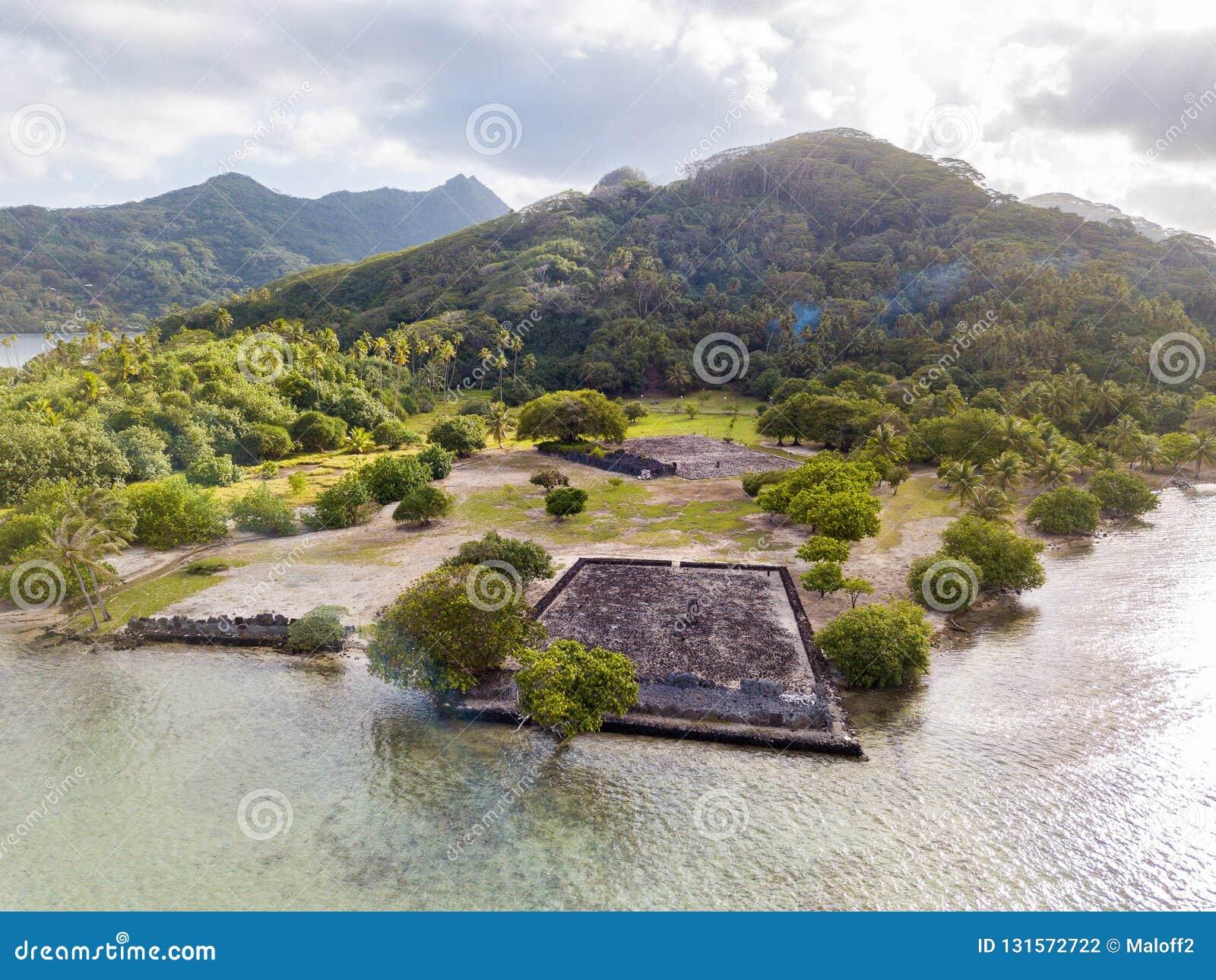 Alter Tempelkomplex Marae Taputapuatea auf dem Lagunenufer mit Bergen auf Hintergrund Raiatea-Insel Französisch-Polynesien,