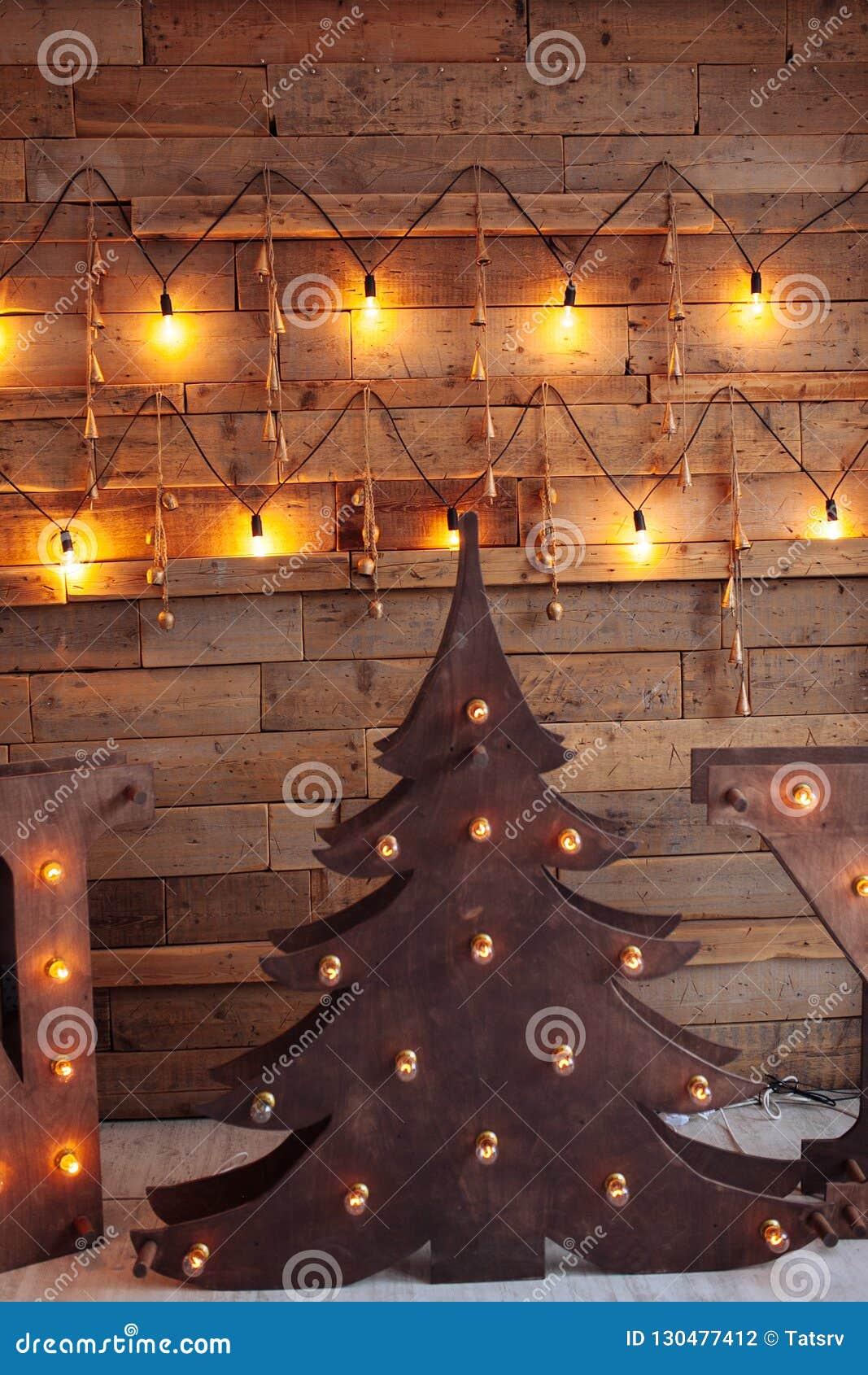 Alternatieve houten Kerstmisboom Een met de hand gemaakte Nieuwjaarboom met gloeilamp op de vloer op houten achtergrond loft