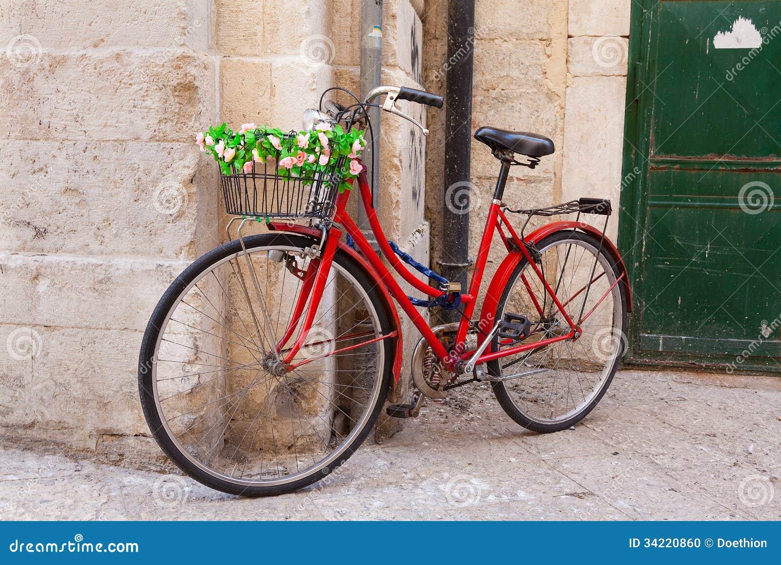 altes fahrrad mit dem korb bedeckt mit den blumen die auf. Black Bedroom Furniture Sets. Home Design Ideas