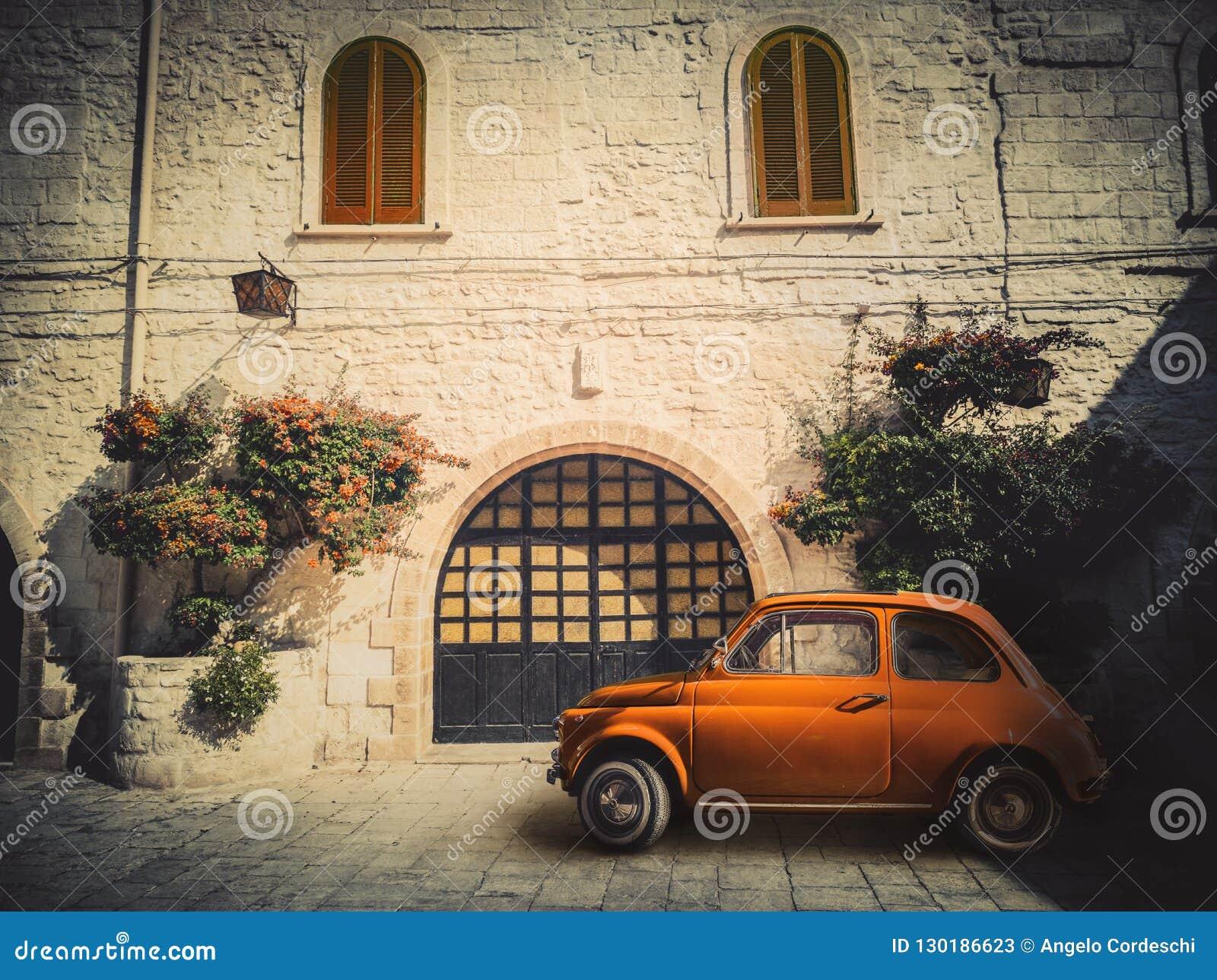 Altes kleines orange italienisches Auto, geparkt auf der Straße vor einer alten Wohnung