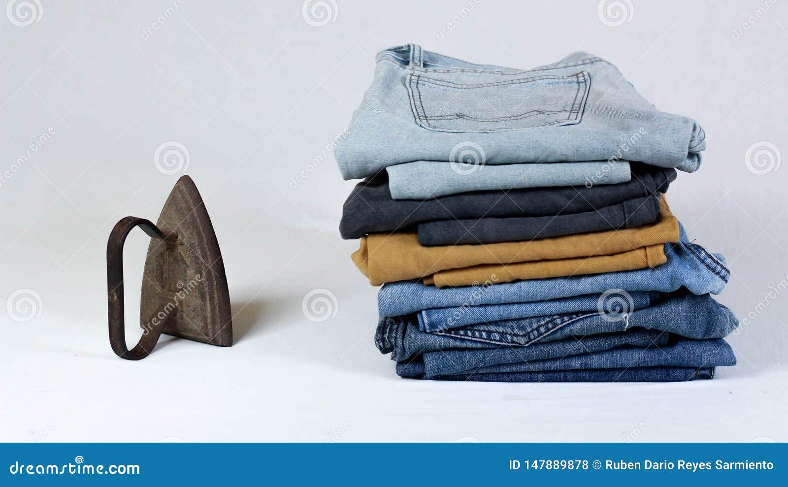 Altes Pl?tteisen mit Jeans auf wei?em Hintergrund