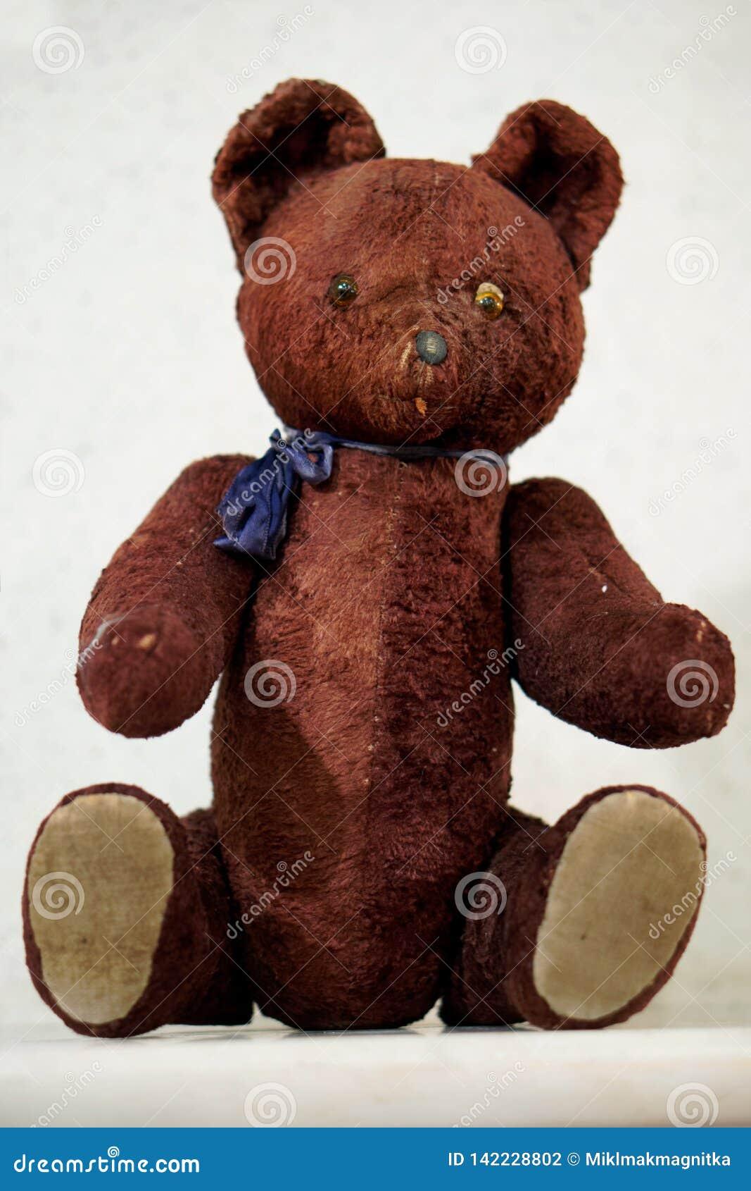 Altes Spielzeug - ein Weinleseplüschbraunbär sitzt auf dem Kaminsims