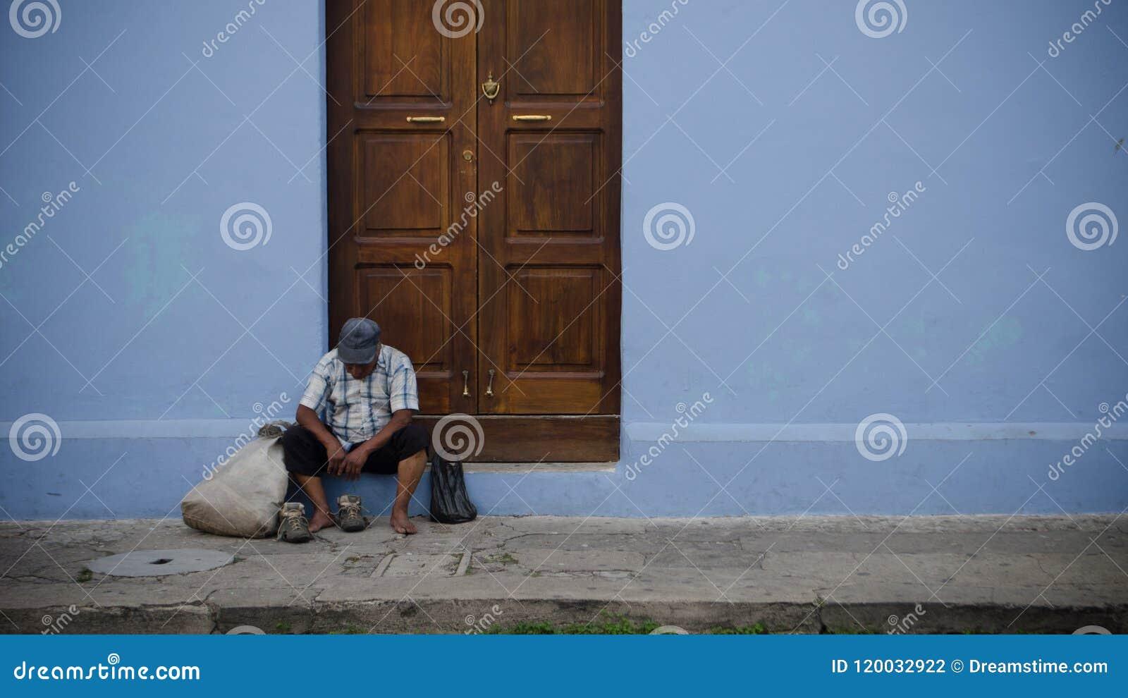 Altes und trauriges obdachloses Sitzen auf der Straße
