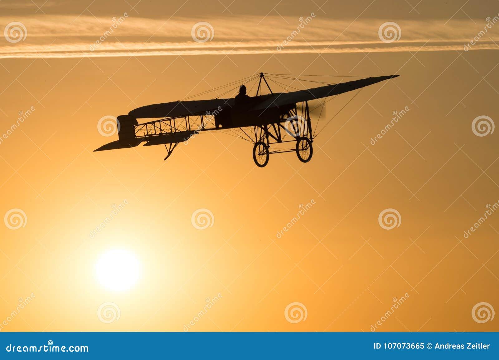 Altes Weinleseflugzeugfliegen in einem orange Himmel bei Sonnenuntergang