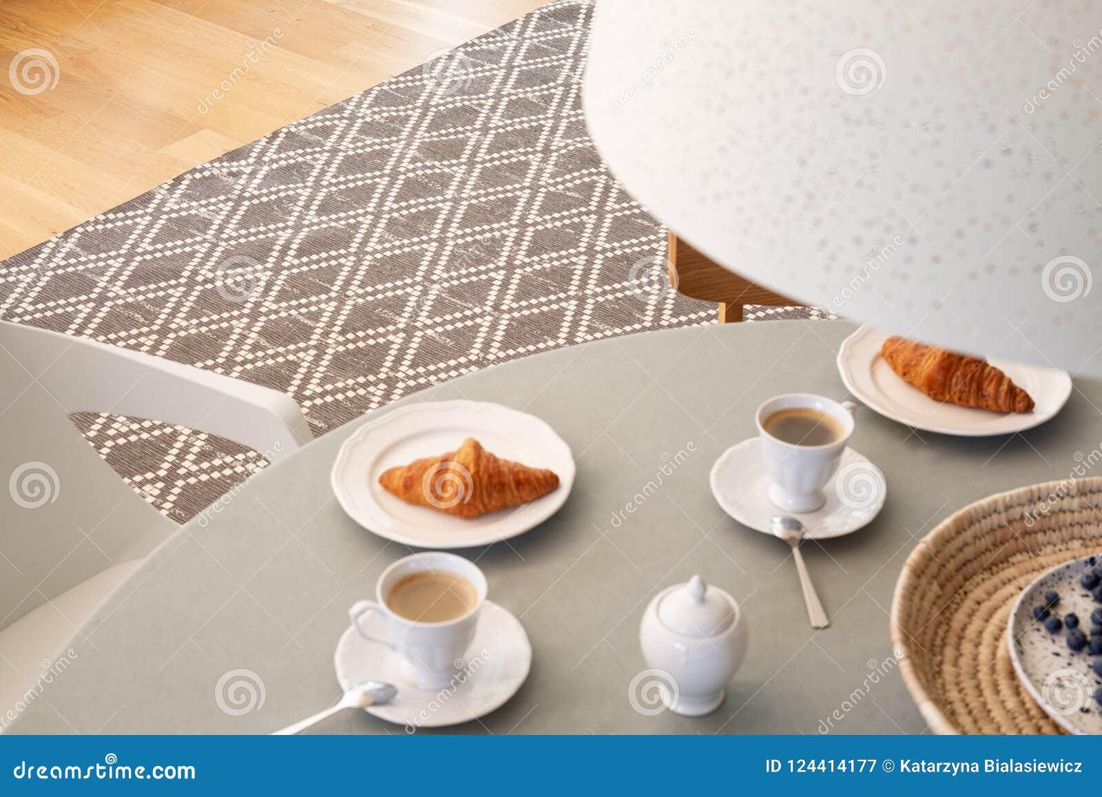 Alto ángulo en la tabla gris con las tazas y los cruasanes en dini del scandi