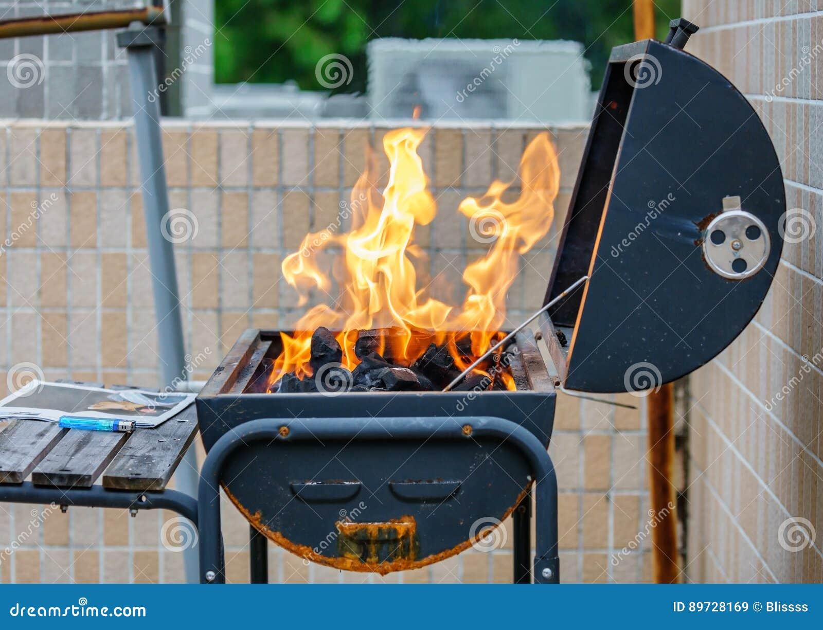 Alto ardiendo del fuego en una estufa Barbacoa al aire libre que cocina en una comida campestre en el verano