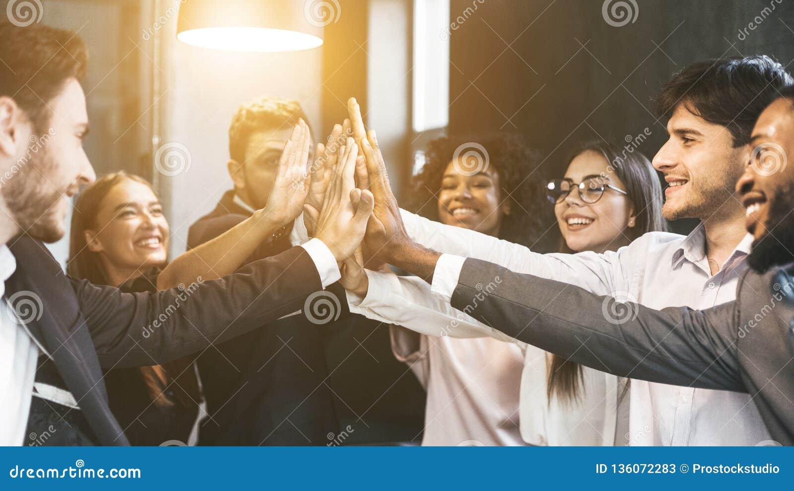 Alto-cinco para o sucesso Grupo diverso de colegas do negócio no escritório