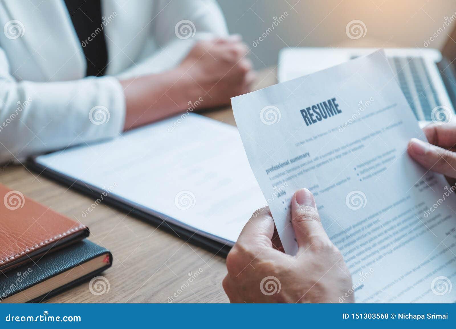 Alto directivo hora que lee un curriculum vitae durante un candidato y un reclutamiento de la reunión del hombre joven del emplea