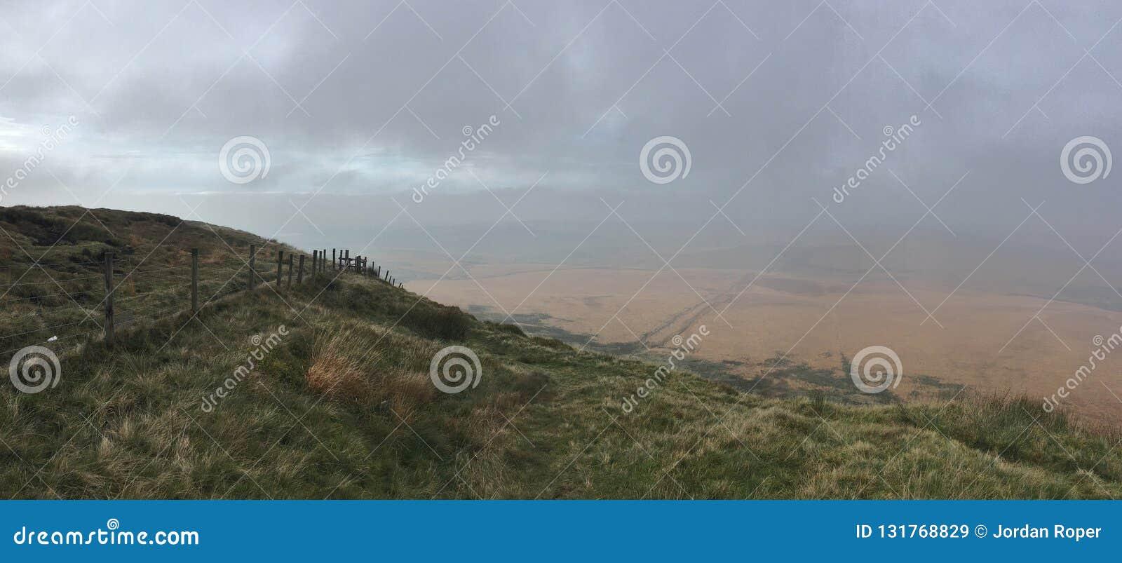 Alto nelle colline che esaminano giorno nuvoloso/nebbioso di vista del campo, contenuto il Regno Unito