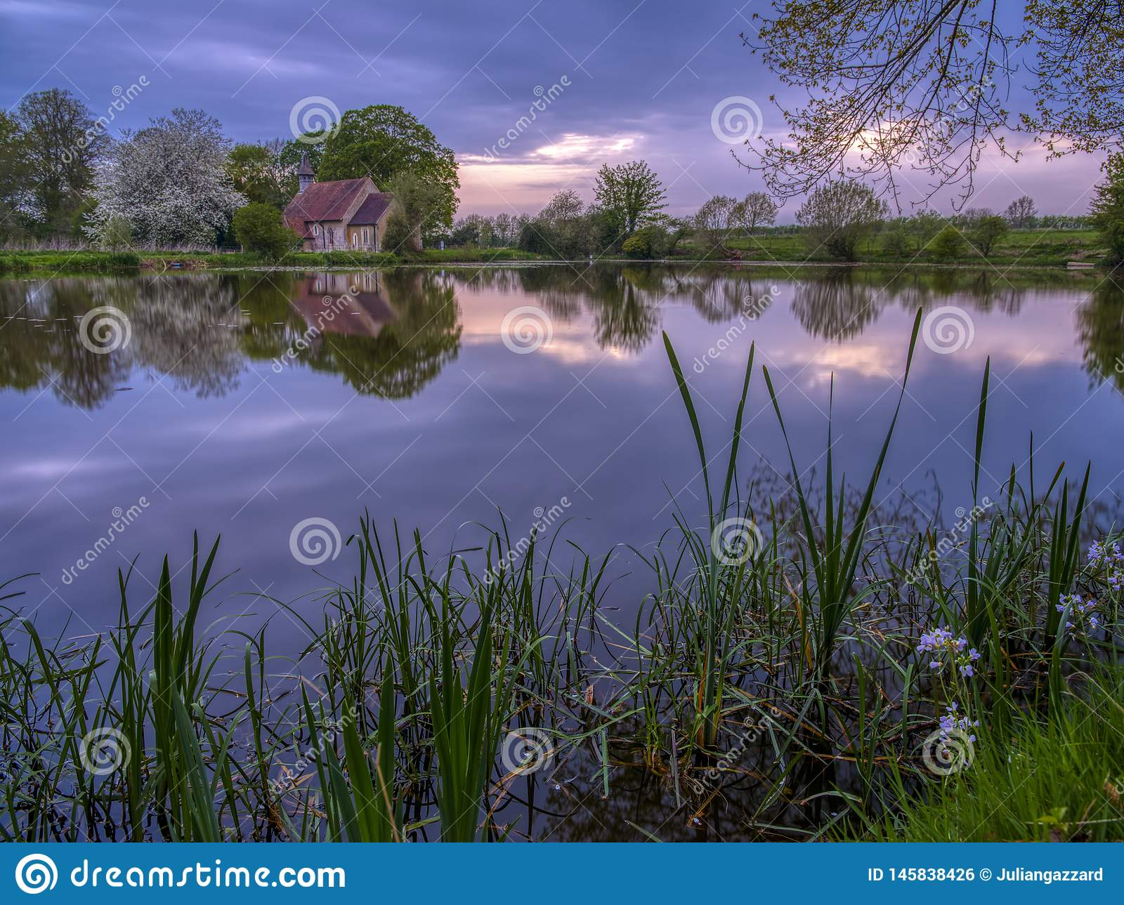 Reflections of St Leonard`s church in Hartley Mauditt Pond, South Downs National Park, UK