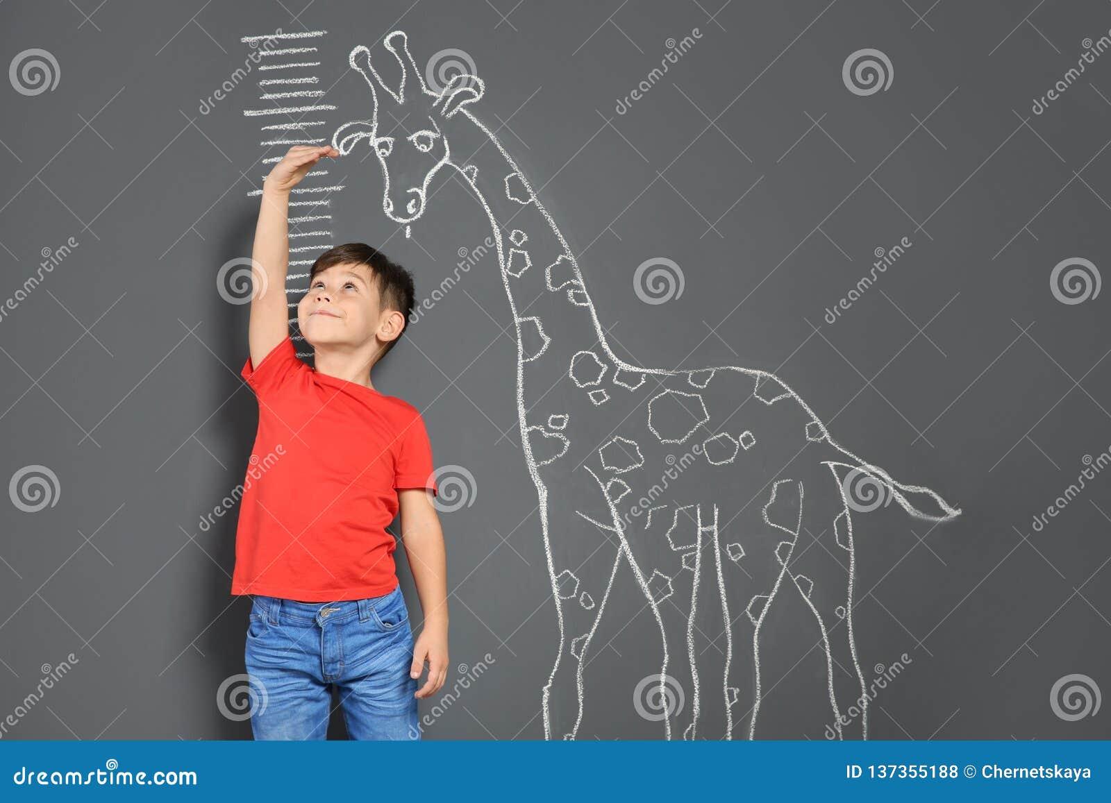 Altura de medição bonito da criança pequena perto do desenho do girafa do giz
