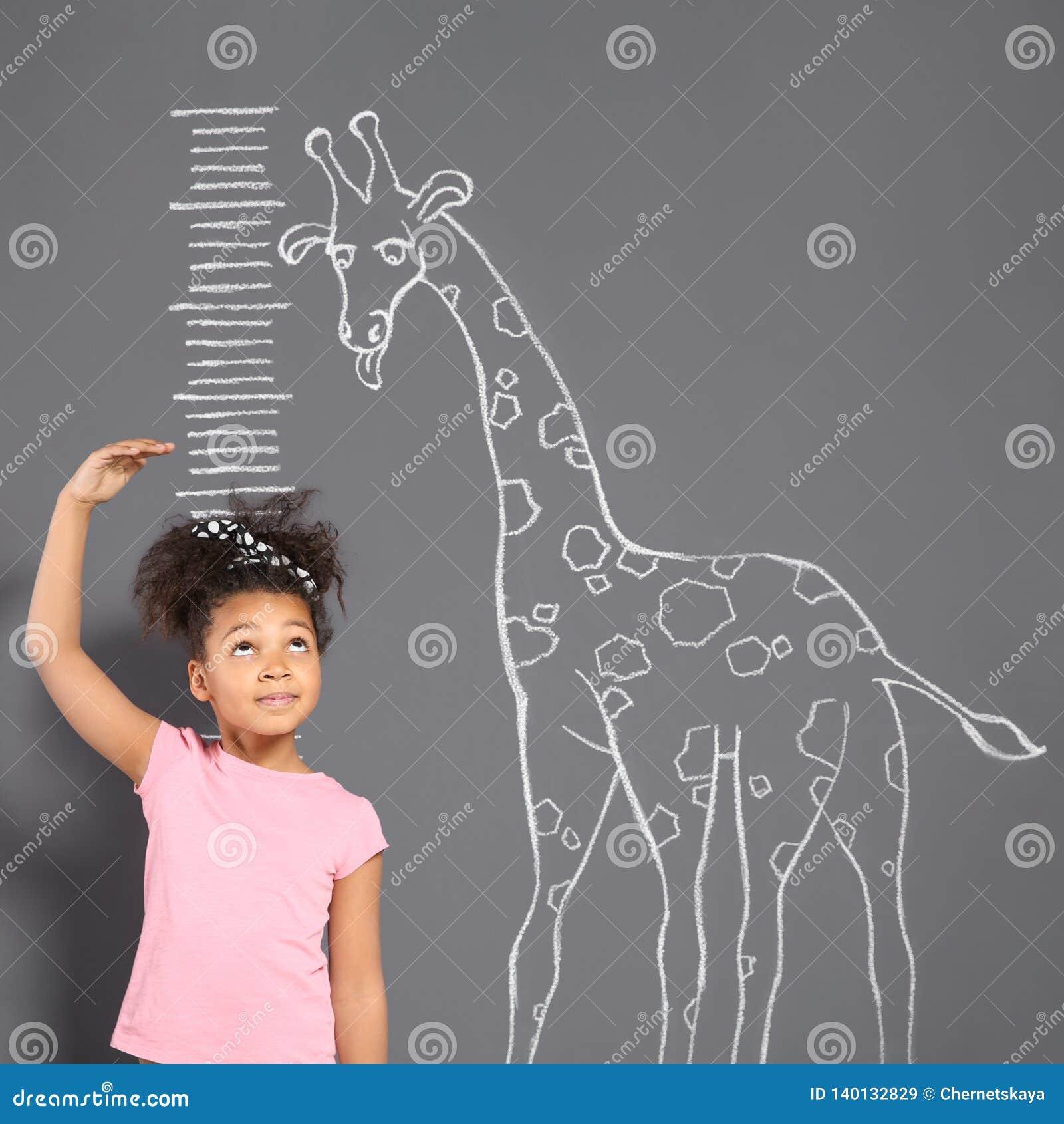 Altura de medição da criança afro-americano perto do desenho do girafa do giz