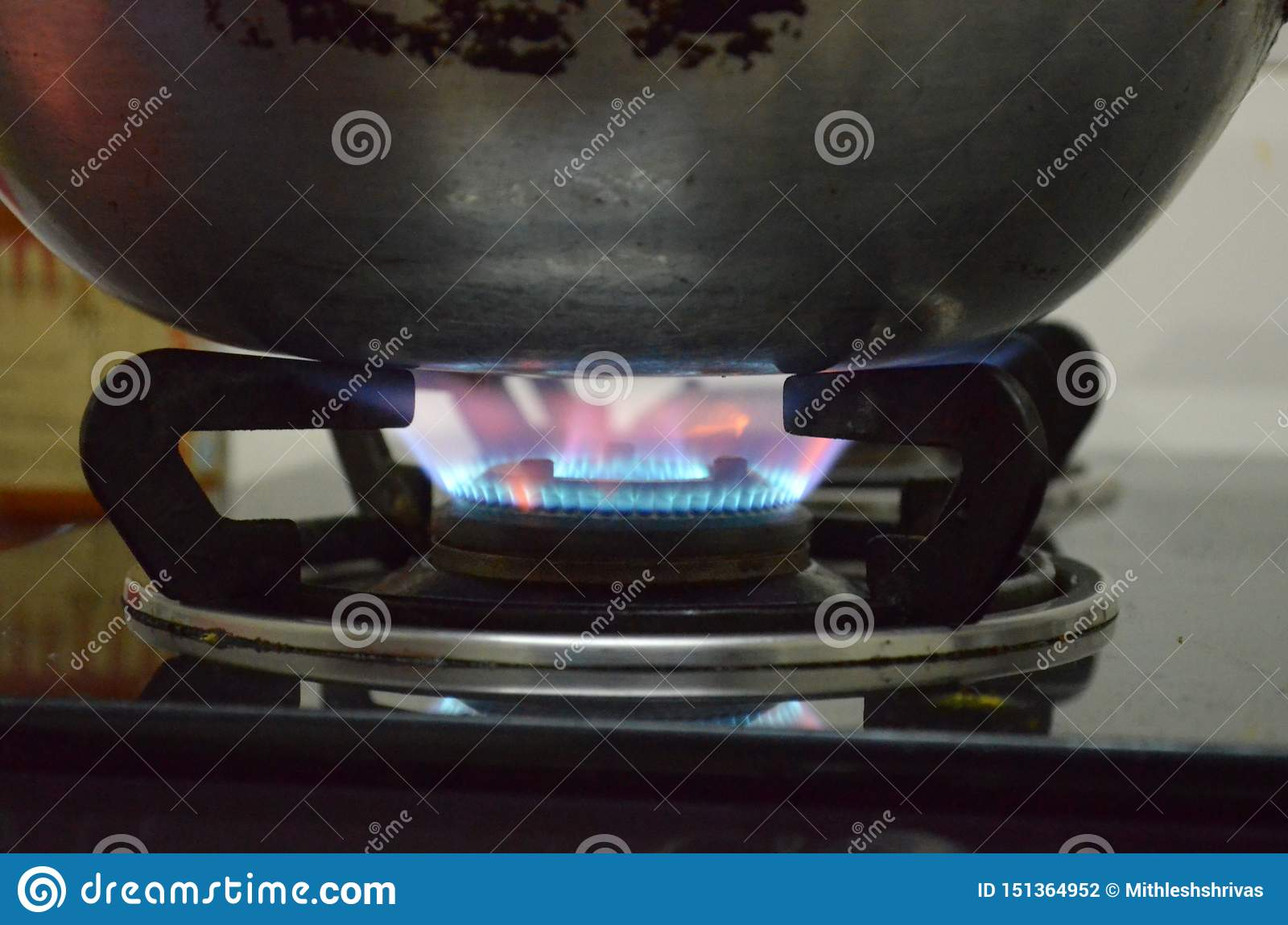 An Aluminium pan under the flames in gas stove; old style cooking