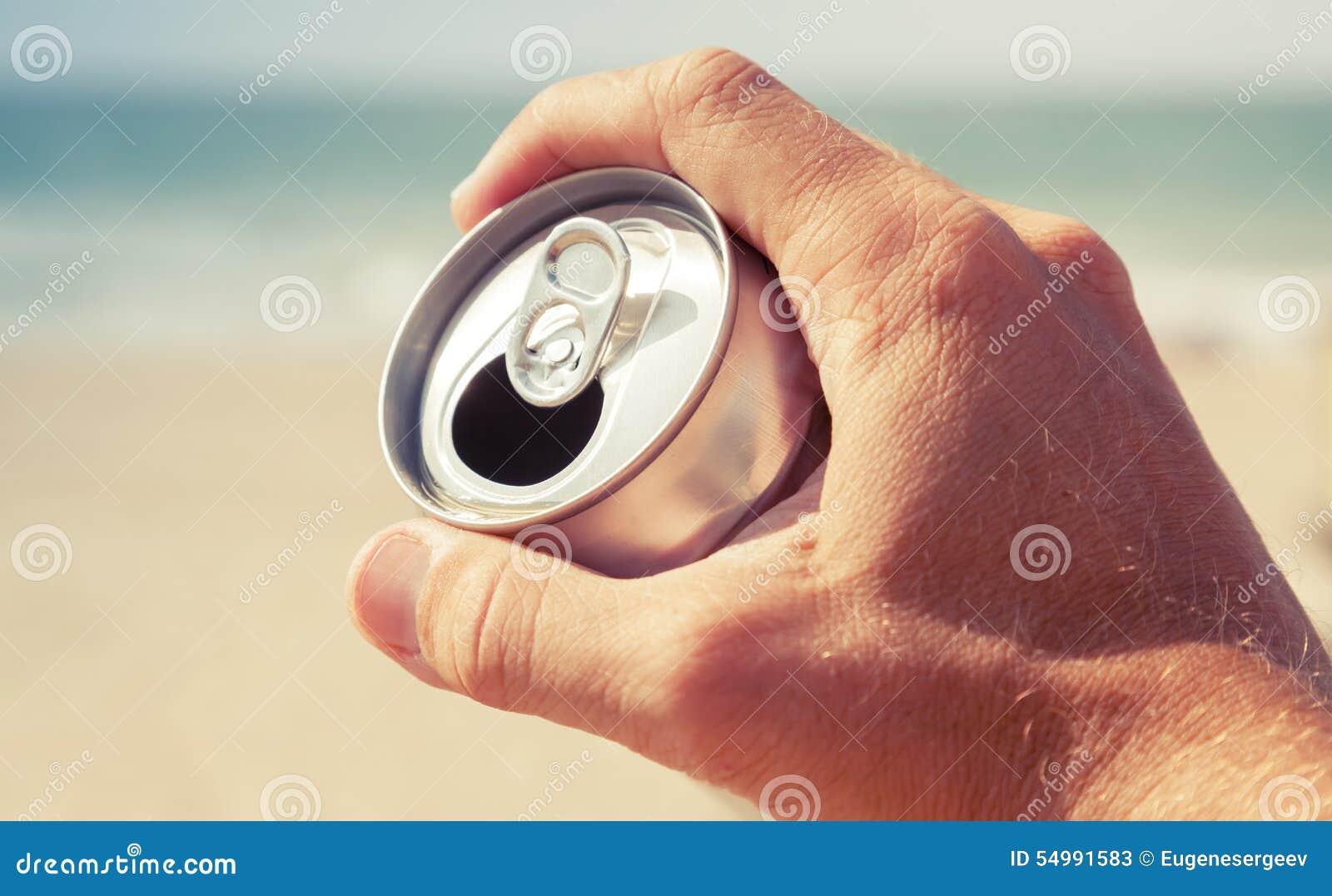 Aluminiumburk av öl i den manliga handen, tonat retro