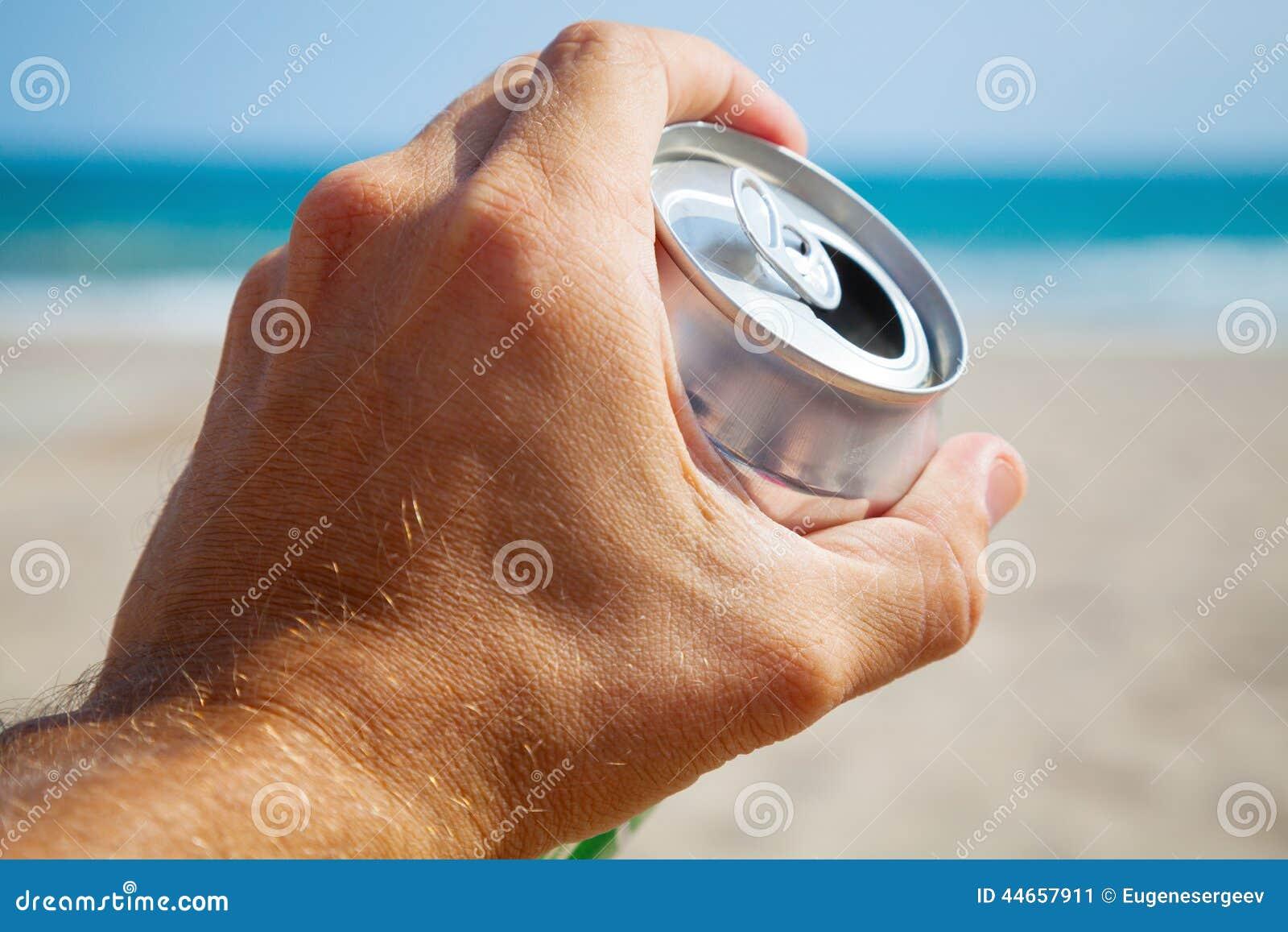 Aluminiumburk av öl i en manligt hand, strand och hav