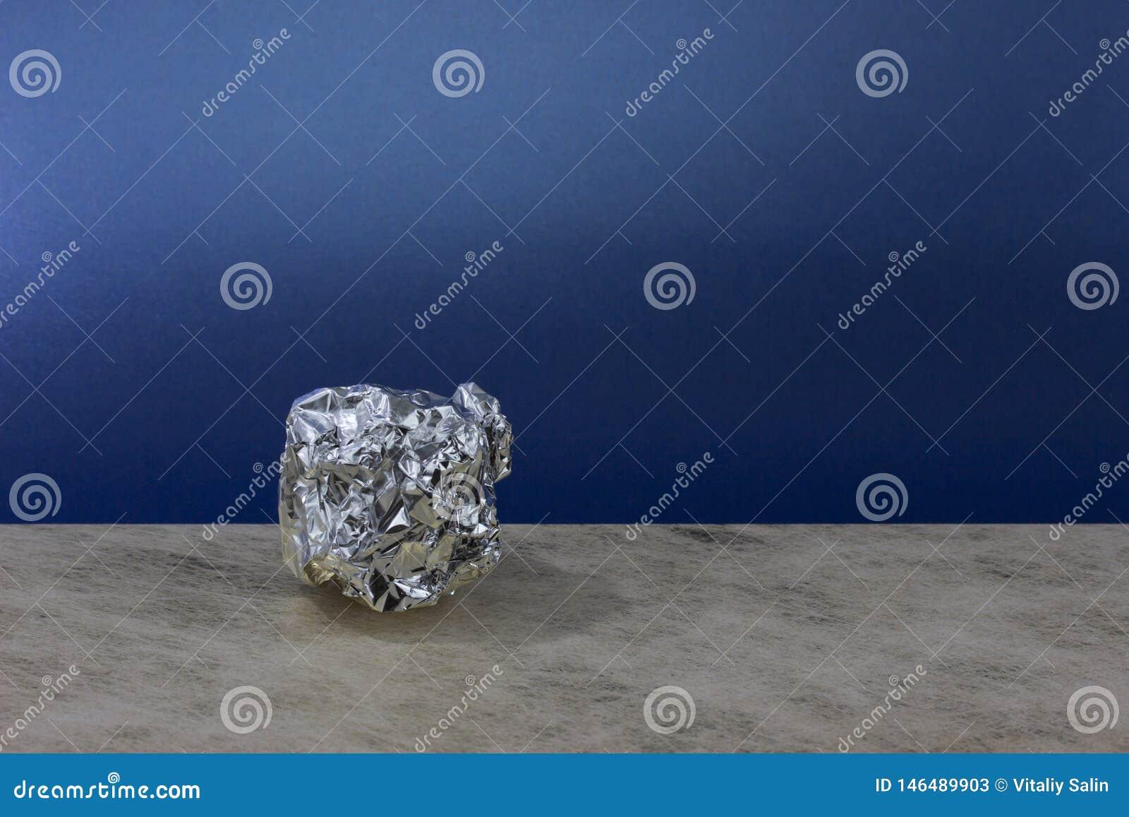 Aluminiumfoliebal op blauwe achtergrond