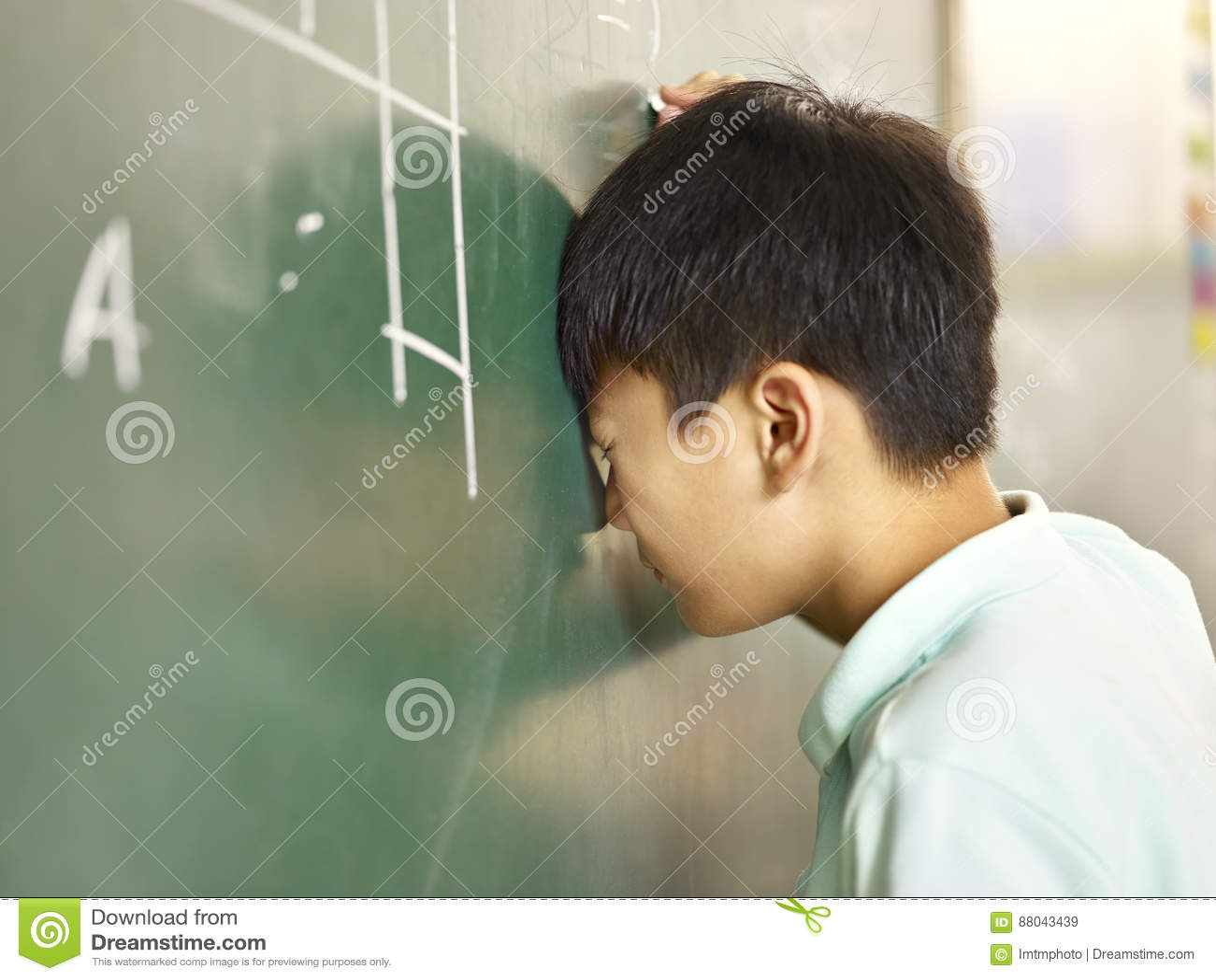 Alumno asiático doloroso que golpea su cabeza en la pizarra