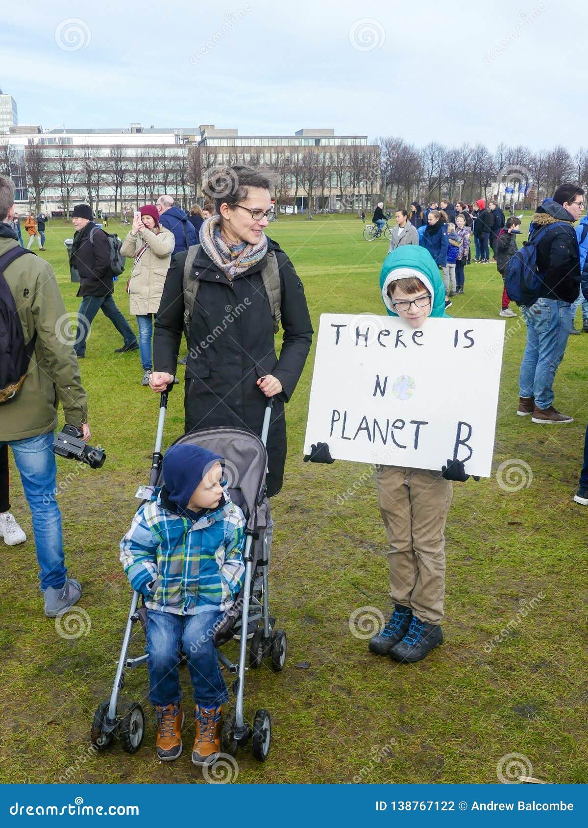 Alumno en la protesta anti del cambio de clima en La Haya con las banderas que camina a través de la ciudad