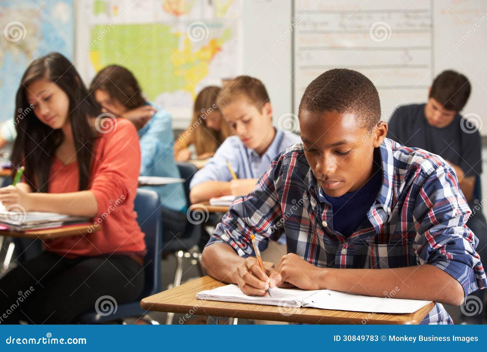 Alumno masculino que estudia en el escritorio en sala de clase
