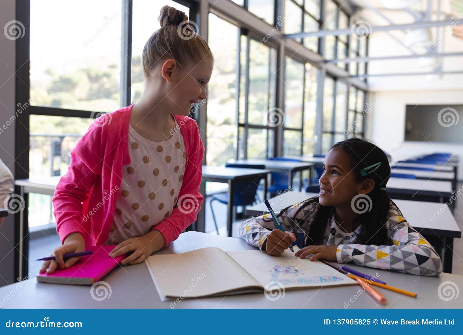 Alumnos que hablan con uno a en el escritorio en sala de clase