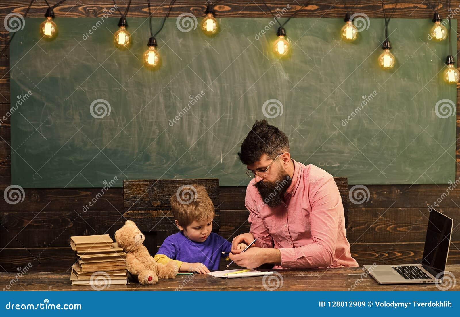 Aluno com o professor na escola Criança de ajuda do tutor para escrever letras no caderno O homem e o menino sentam-se na mesa co