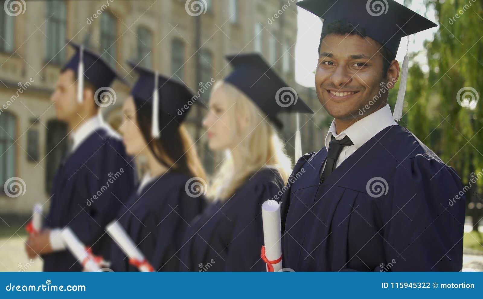 aluno diplomado da Misturado-raça com diploma que sorri na câmera, programa da troca vídeos de arquivo