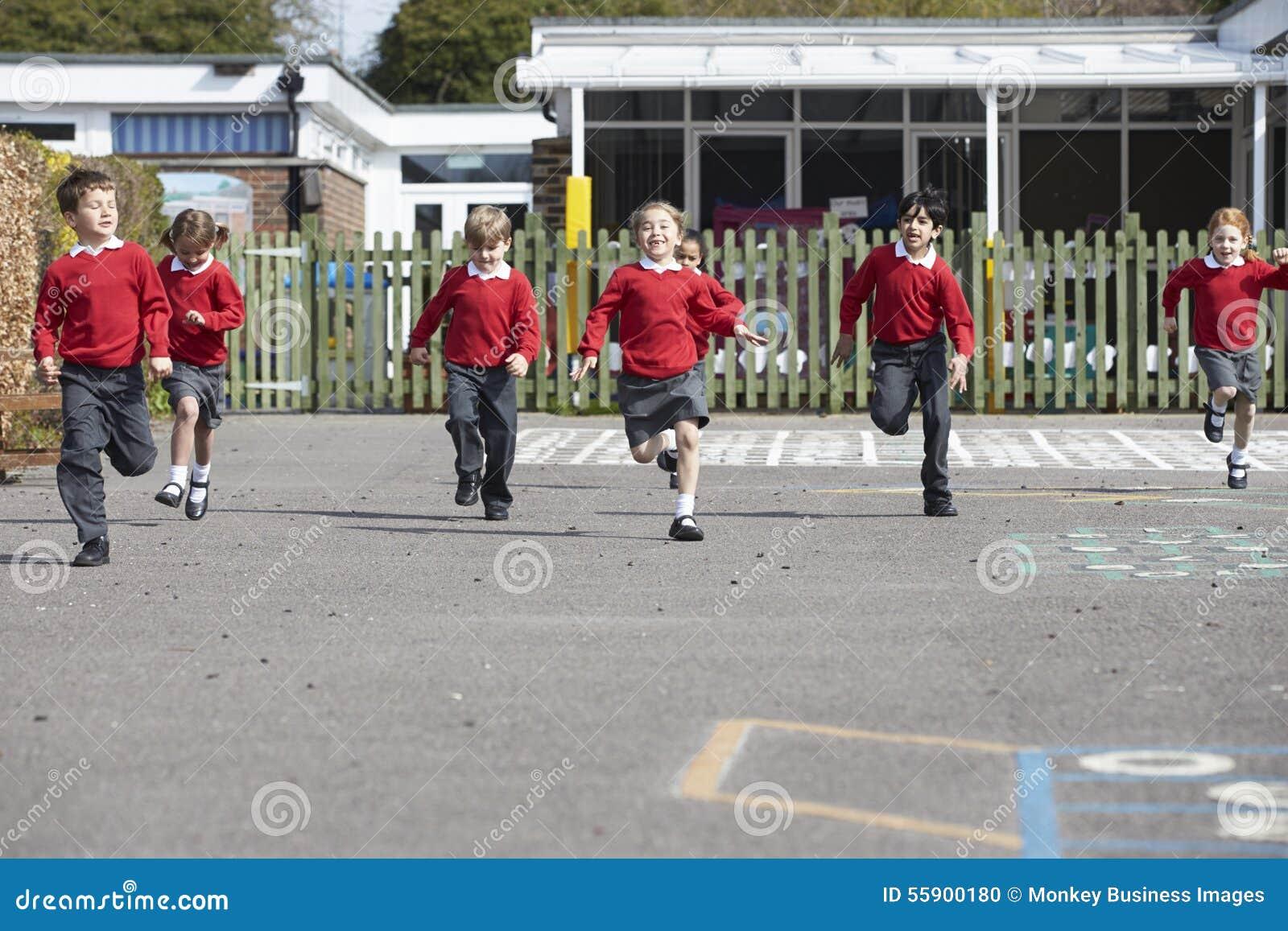 Alunos da escola primária que correm no campo de jogos