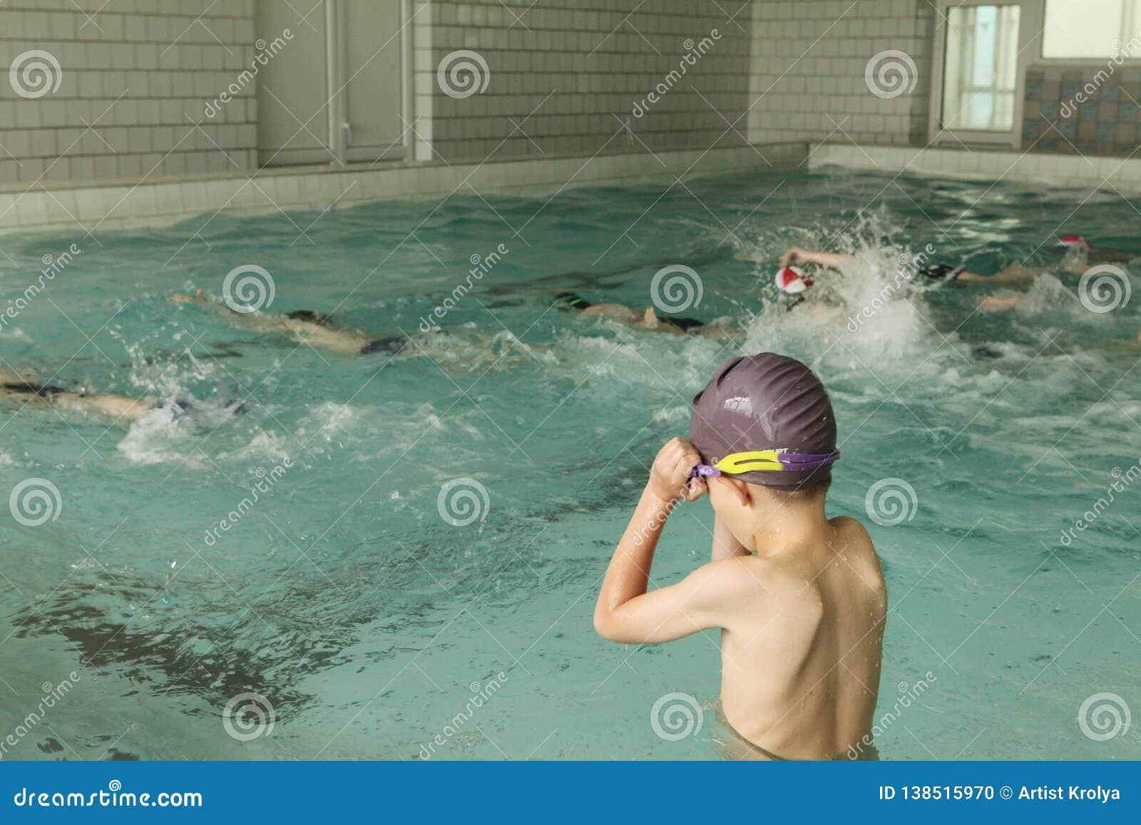 Alunos elementares dentro da lição nadadora das habilidades