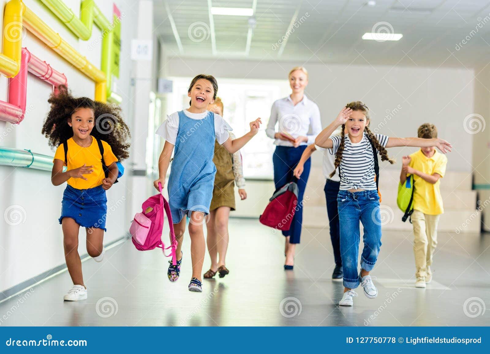 Alunos felizes adoráveis que correm pelo corredor da escola junto com o professor