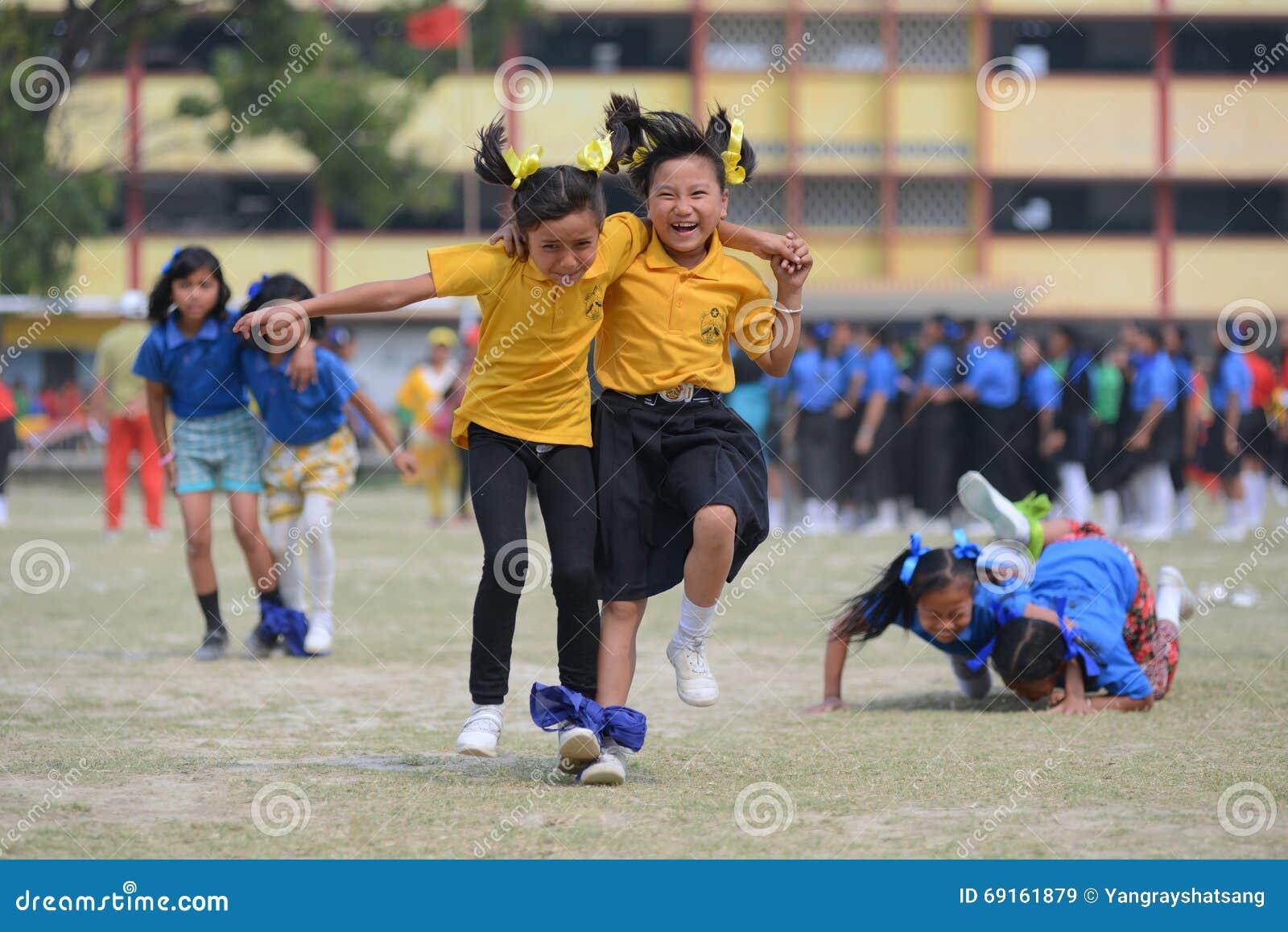 Alunos que participam em uma raça de obstáculo três equipada com pernas