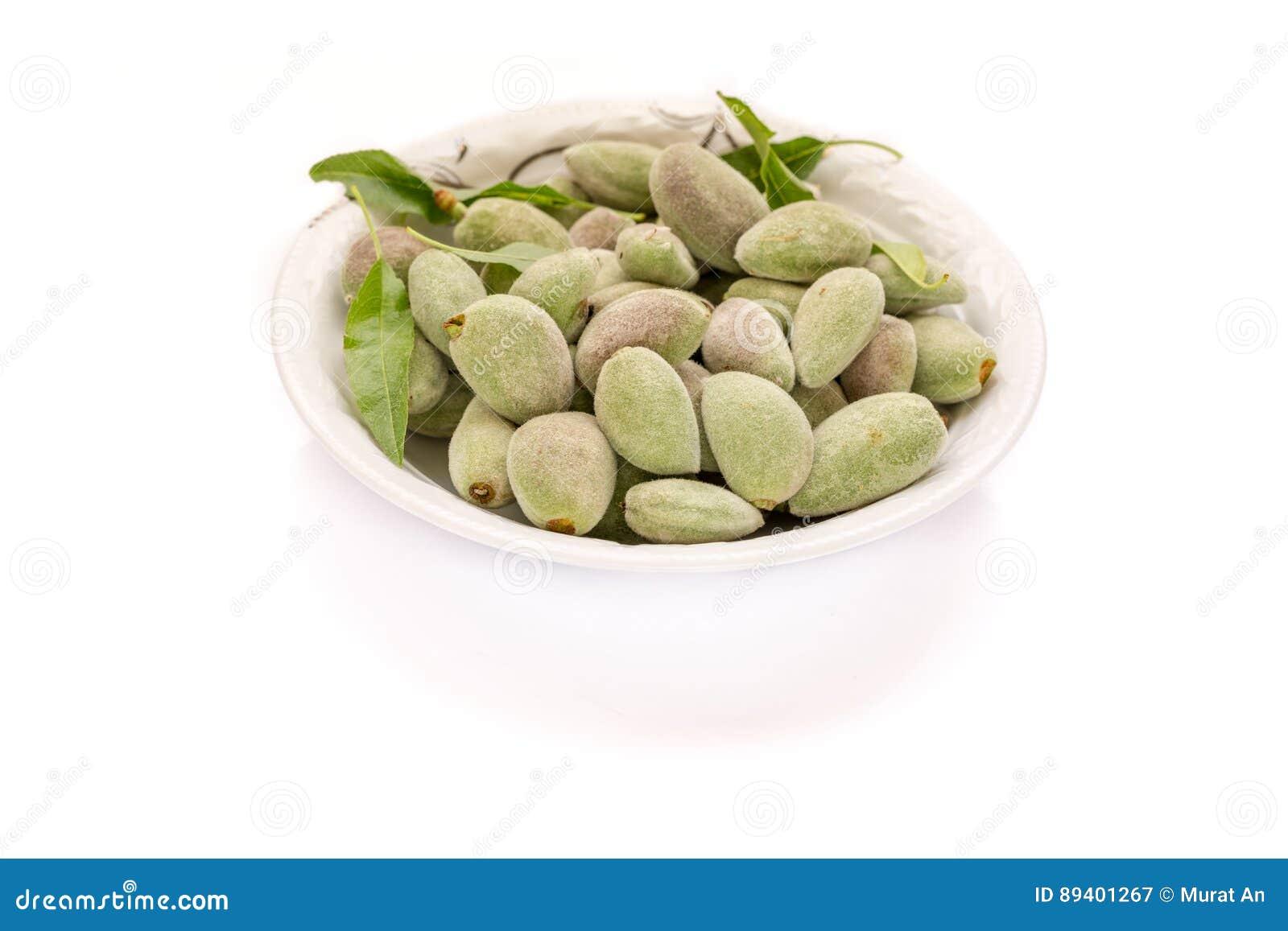 Amêndoas verdes verdes frescas na placa com fundo branco