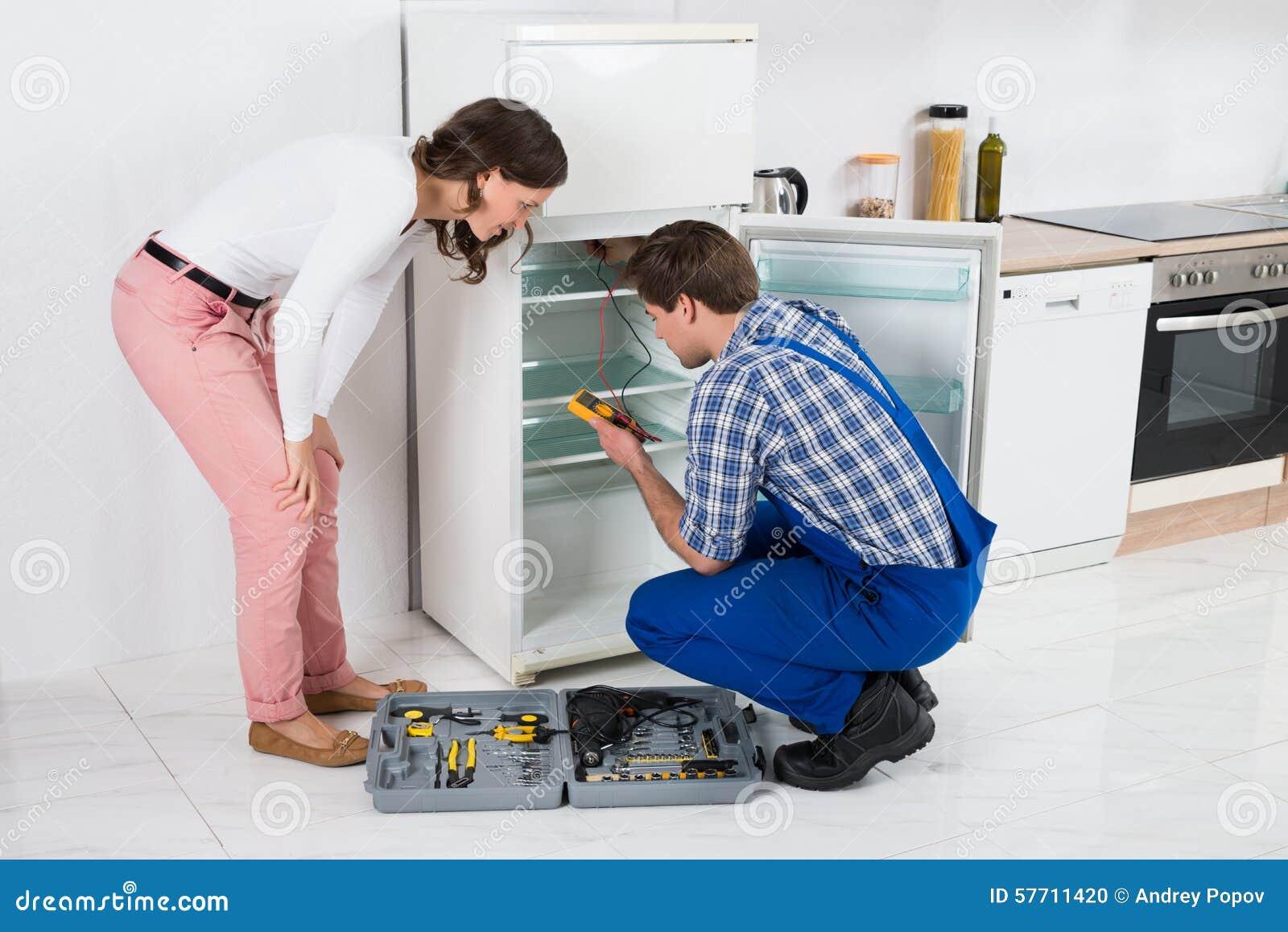 Ama de casa Looking At Worker que repara el refrigerador