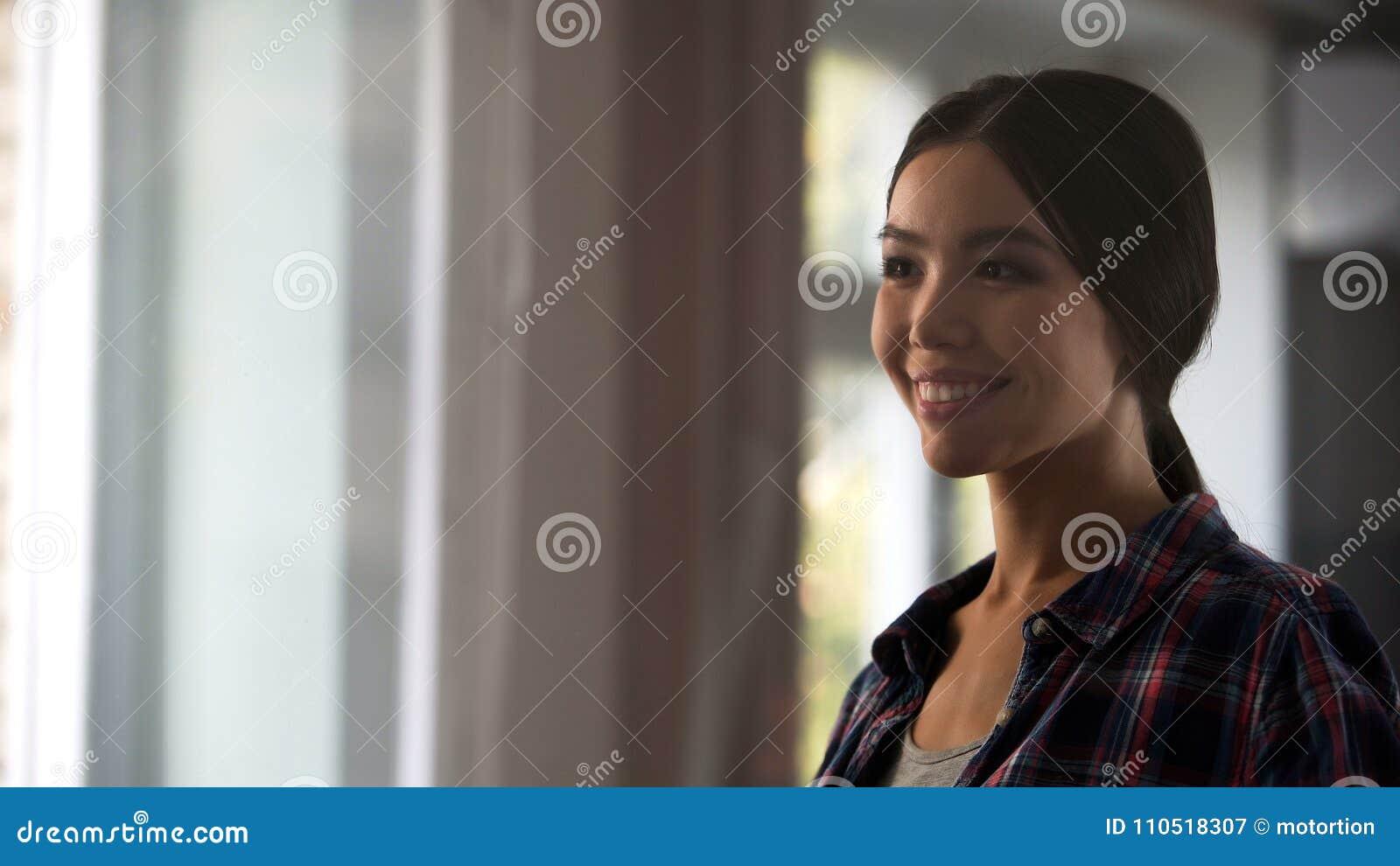 Ama de casa de sexo femenino que mira satisfecha la ventana del sitio después de limpiar, higiene