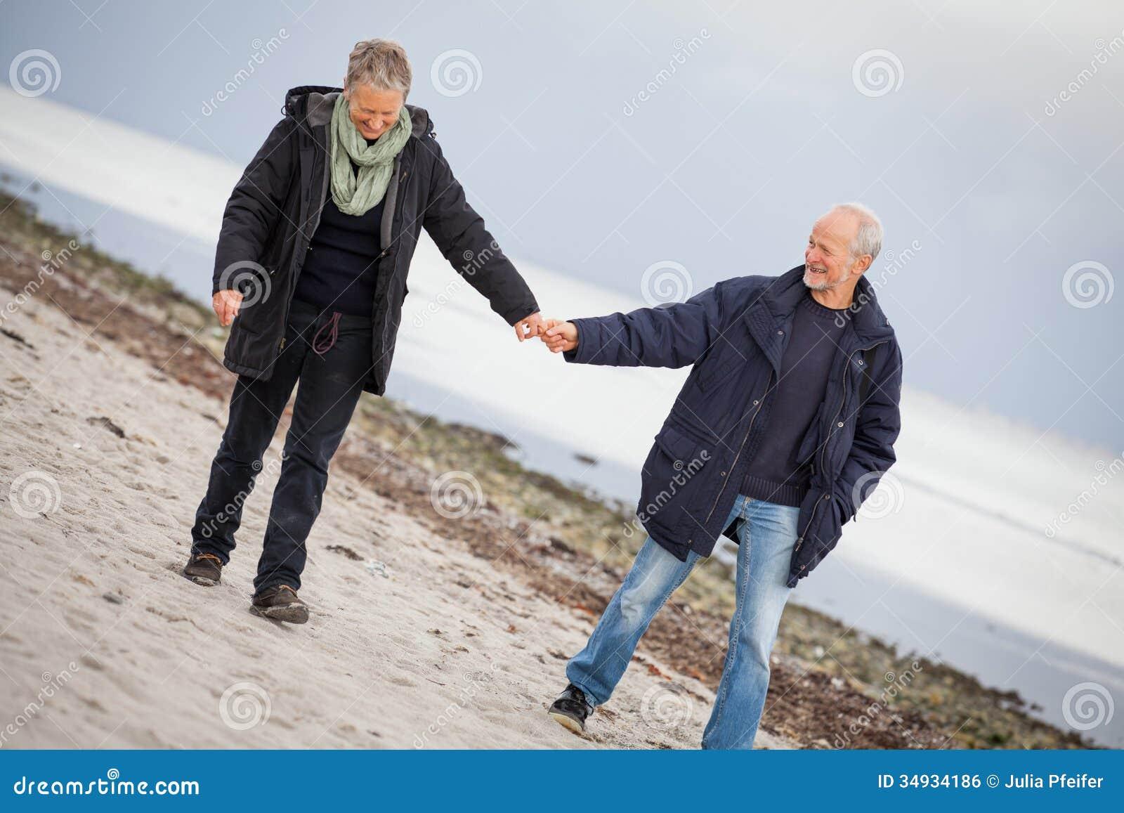 Amadureça os pares felizes que andam na praia no outono
