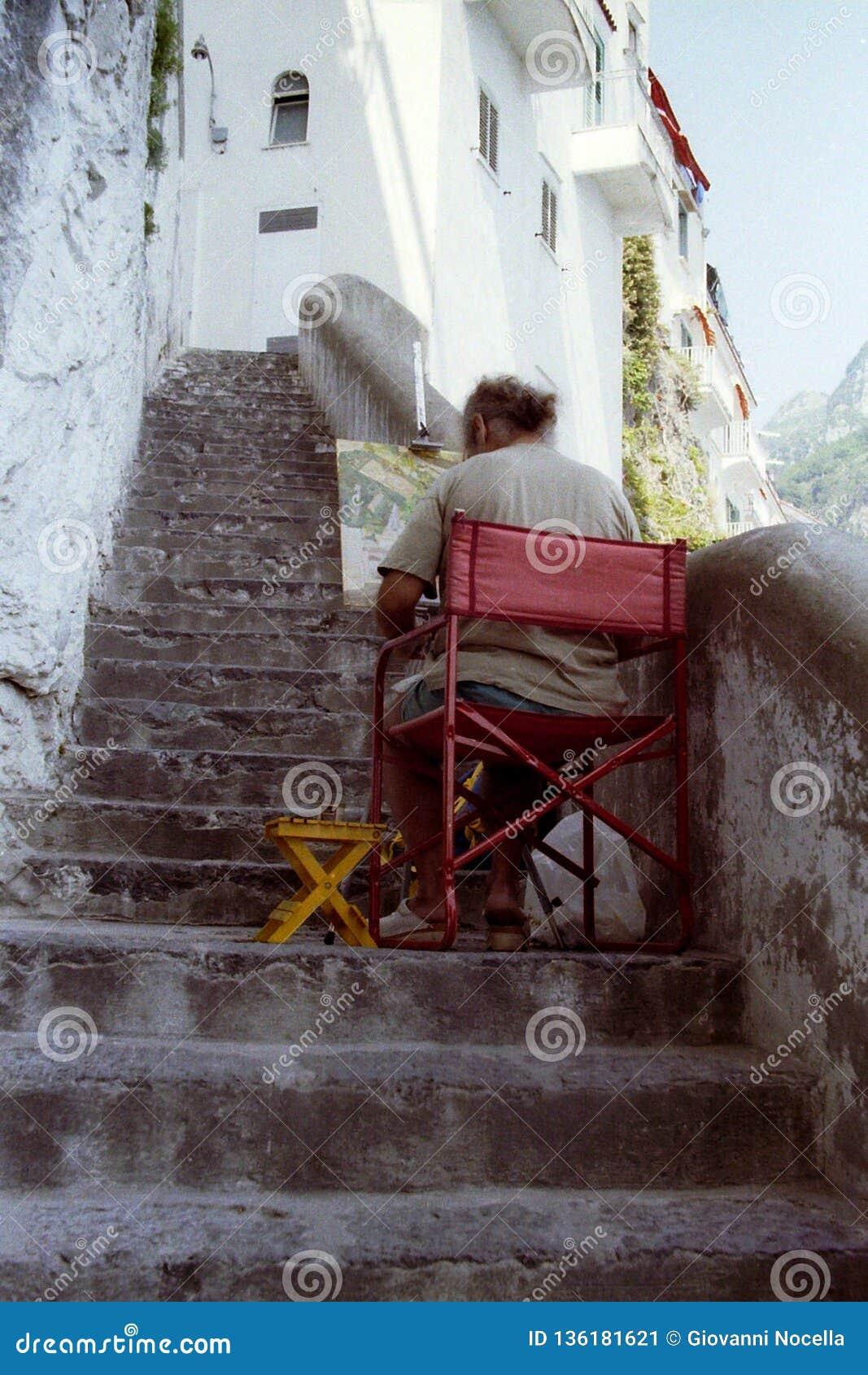 AMALFI ITALIA, 1992 - en målare som tyst ner sitter en brant trappuppgång, väljer i stillhet färgerna för att måla på hans kanfas