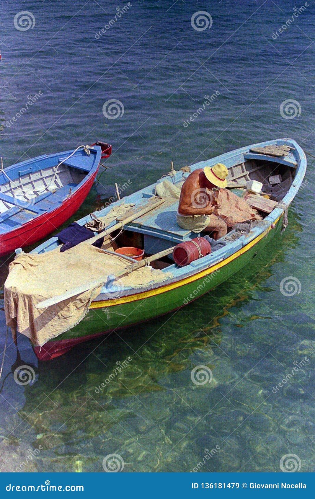AMALFI, ITALIEN, 1974 - älterer Fischer mit sachverständigen Handreparaturen das Netz auf Fischerboot im schönen Meer von Amalfi