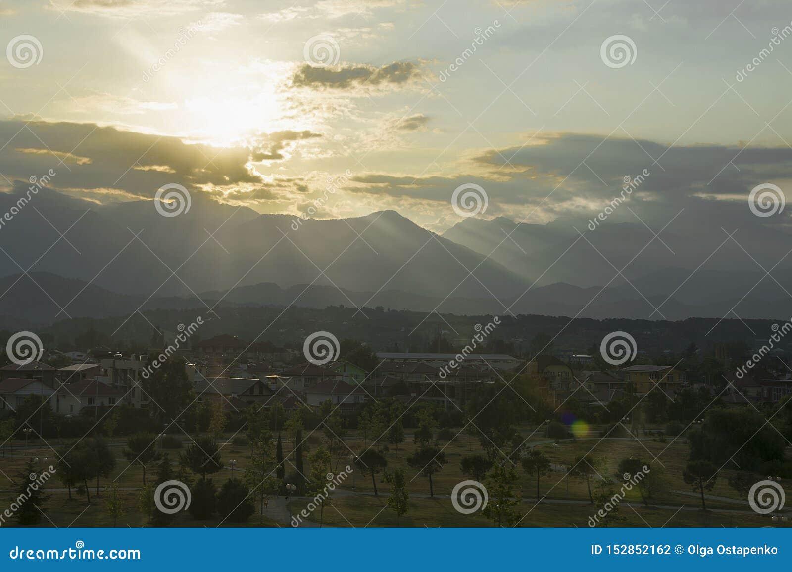 Amanece el sol de detrás las montañas una hermosa vista del pueblo del verano de las palmeras