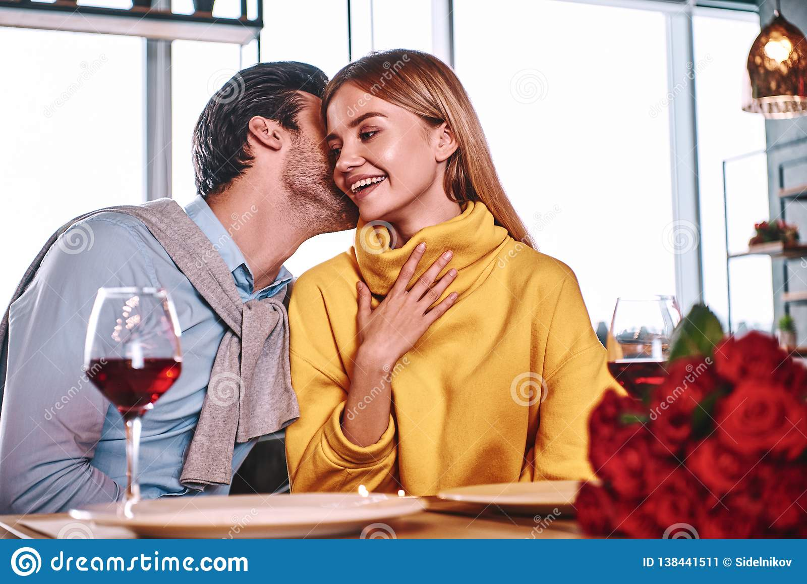 Amantes al principio de la historia de amor - susurros hermosos del hombre en oído bonito de la mujer
