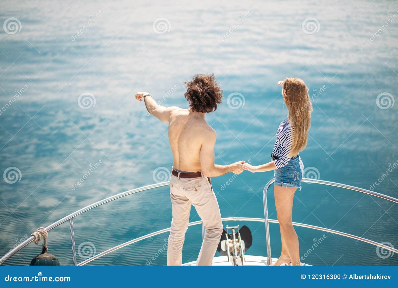 Amantes apasionados que bailan en el arco de la cubierta mientras que navega en el yate