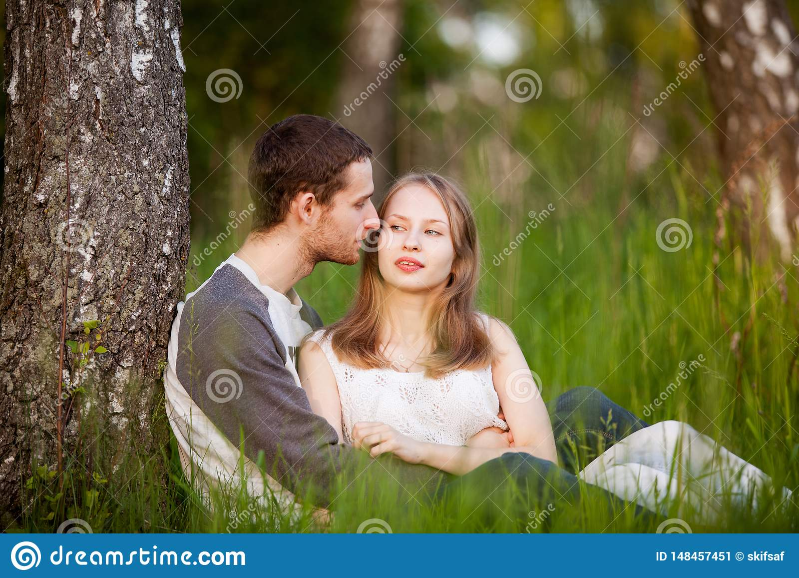 Amantes felices que abrazan en la arboleda del abedul