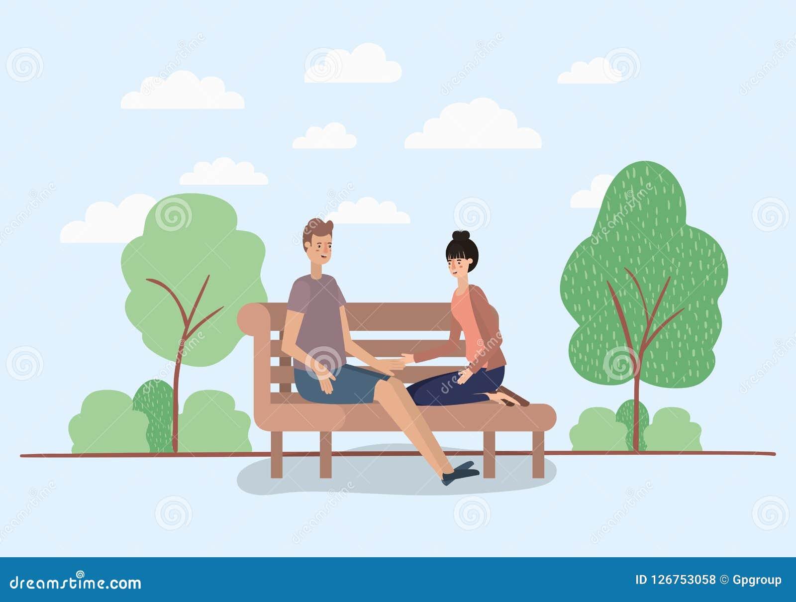Amantes jovenes de los pares que se sientan en silla del parque